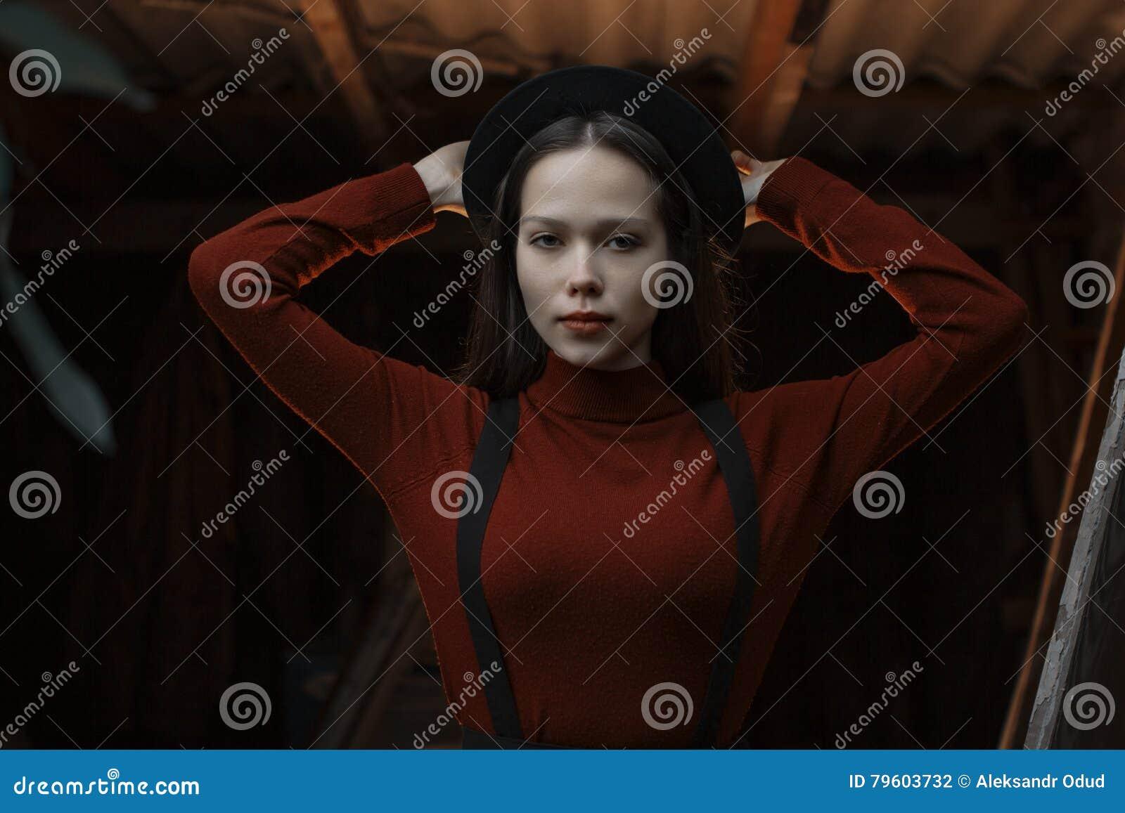 Retrato do close-up do mulheres elegantes novas bonitas Senhora que levanta na obscuridade - fundo cinzento Vestir modelo à moda