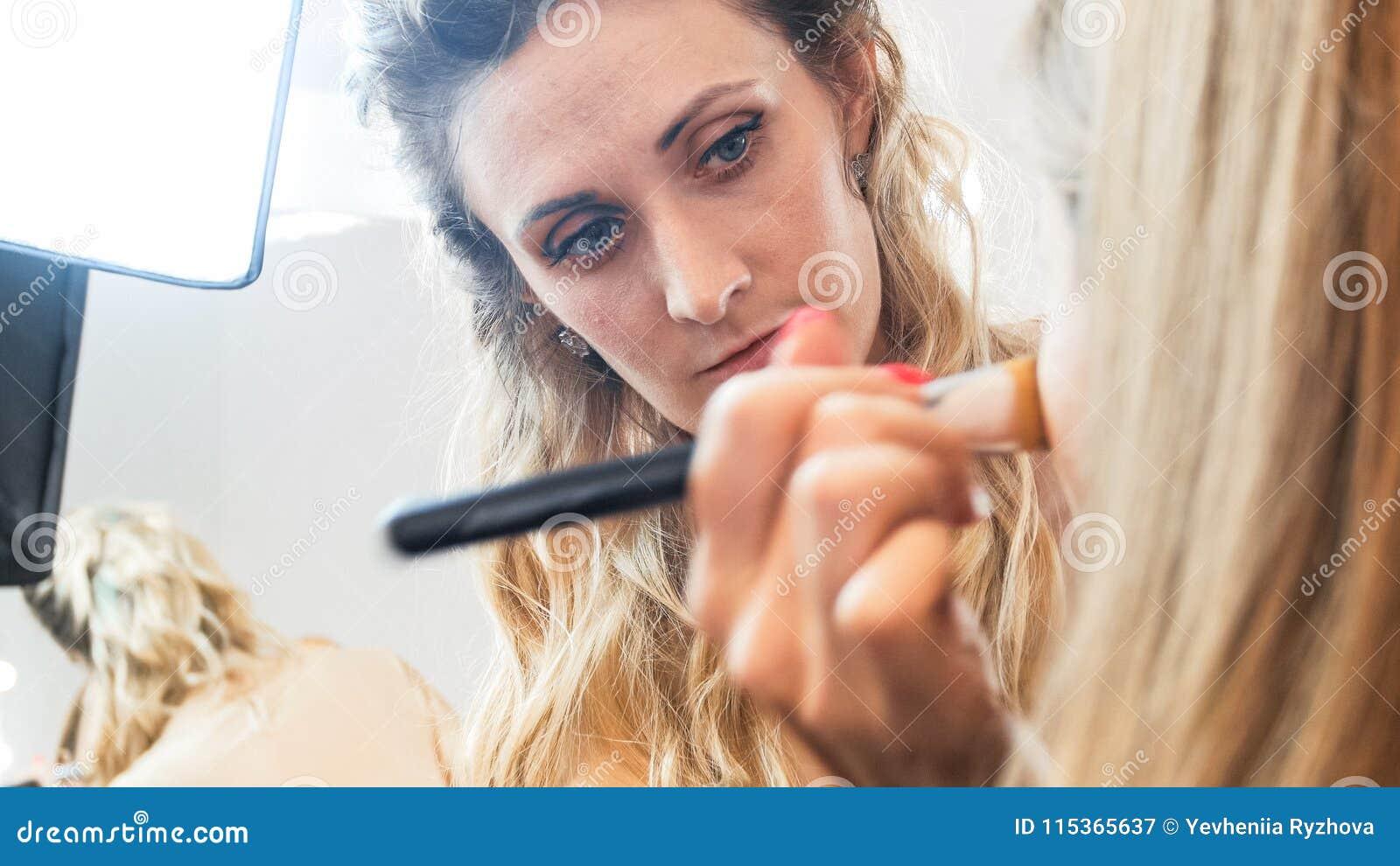 Retrato do close up do maquilhador do profesional que trabalha no estúdio da beleza