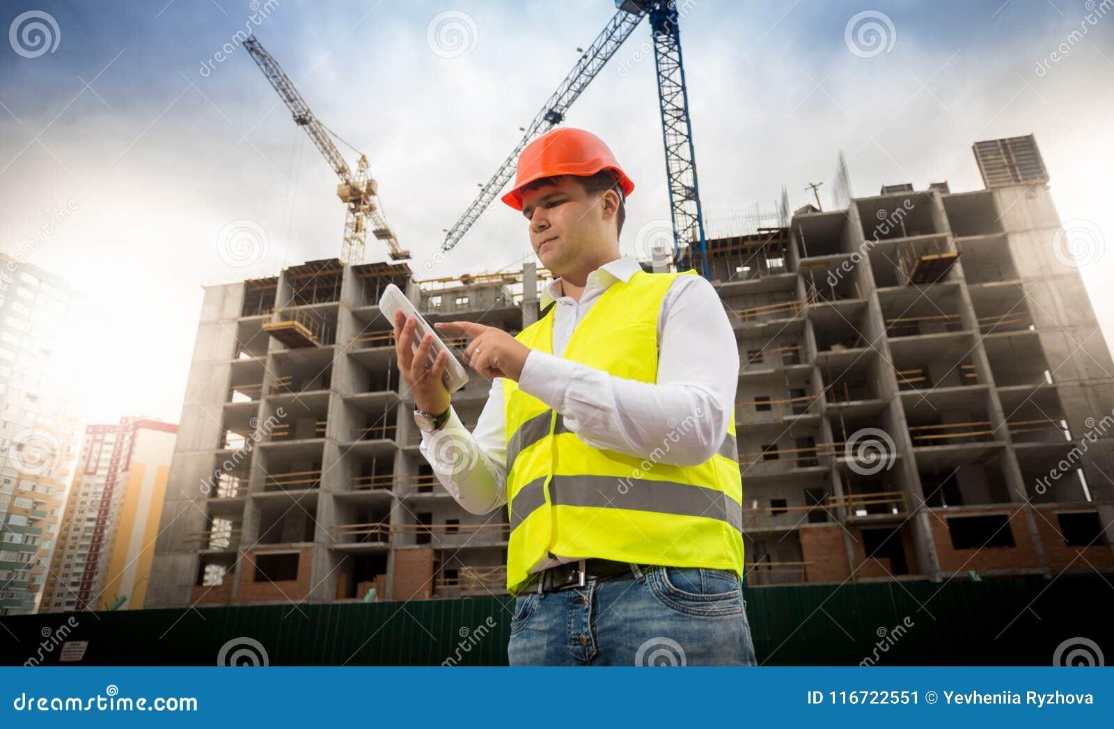 Retrato do coordenador de construção masculino que está no terreno de construção e que usa a tabuleta digital