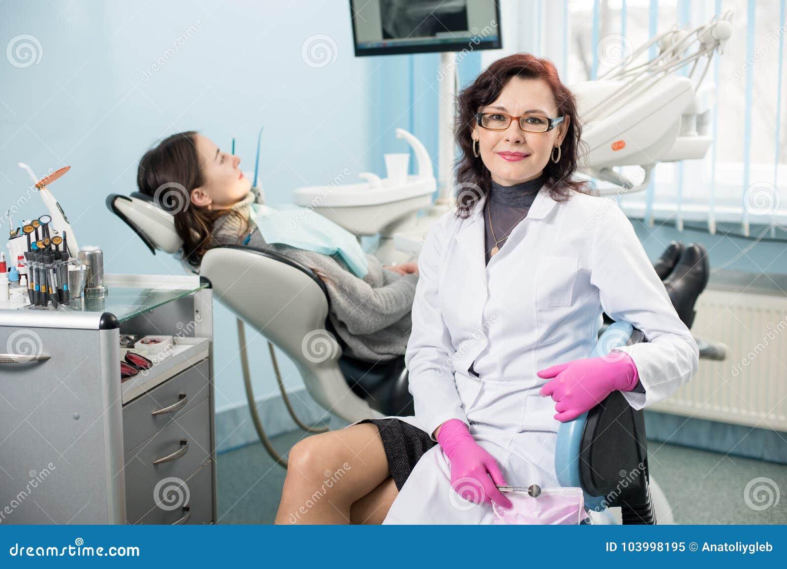 Retrato do dentista fêmea amigável com o paciente da mulher na cadeira na clínica dental