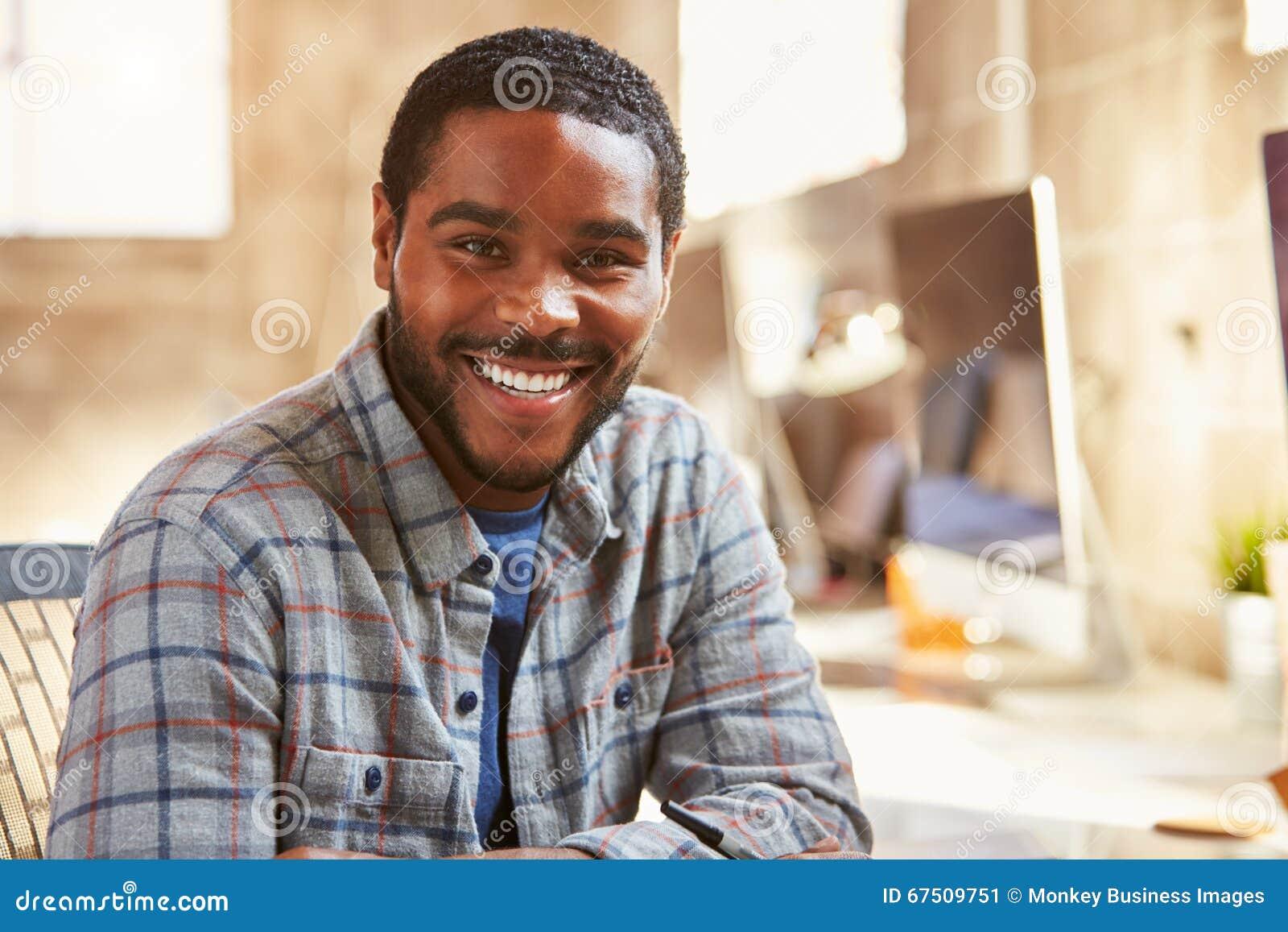 Retrato do desenhista masculino Working At Desk no escritório moderno