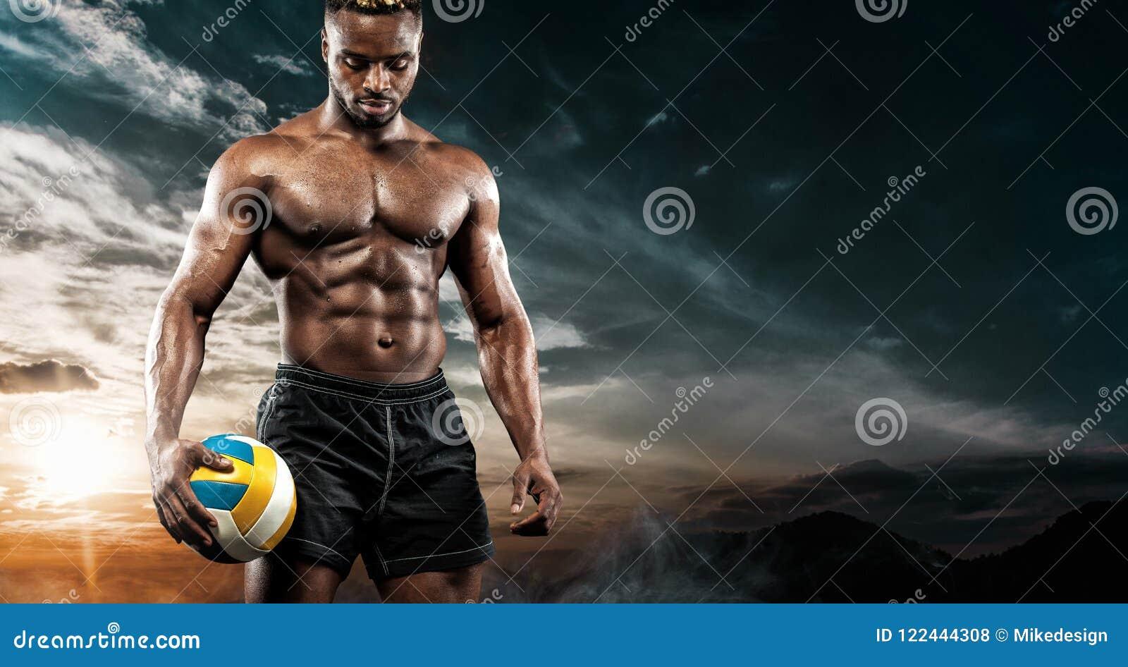 Retrato do desportista afro-americano, jogador de voleibol da praia com uma bola sobre o fundo do céu Homem novo apto dentro