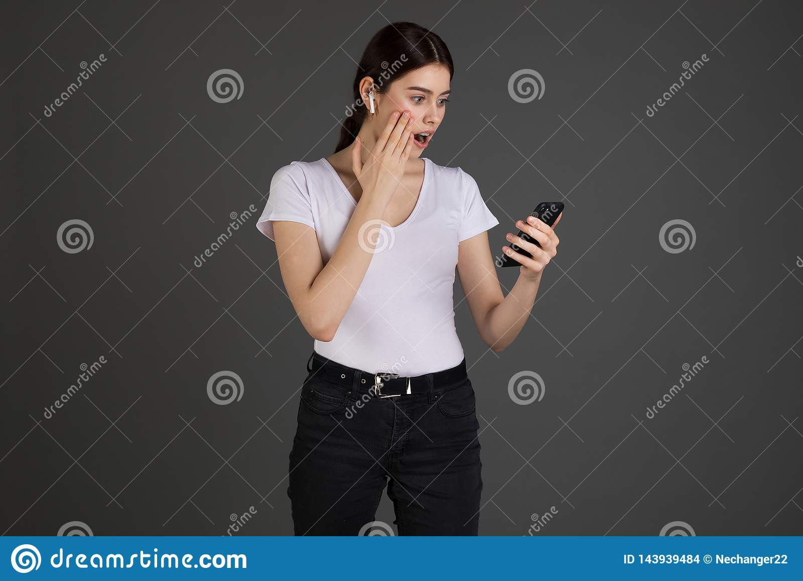 Retrato do estúdio da mulher shoked e confusa que recebe a referência e a mensagem incômoda através da boca aberta do smartphone