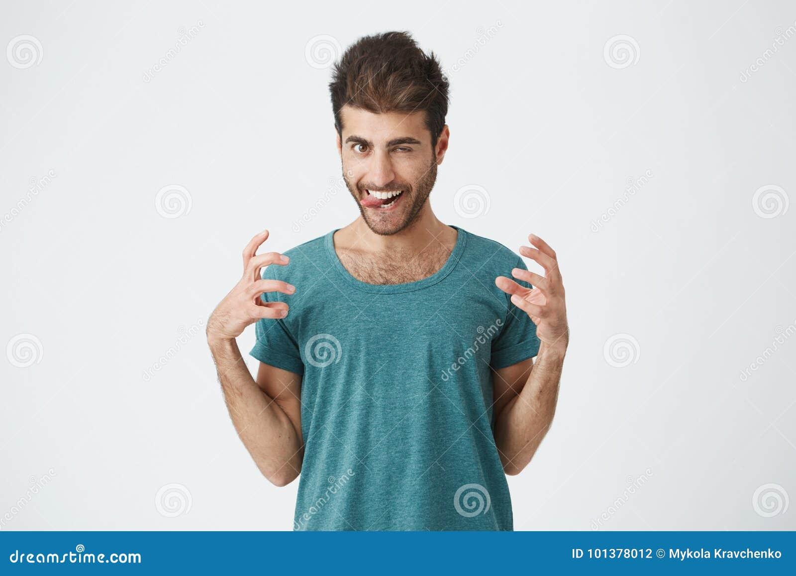 Retrato do estúdio do indivíduo espanhol expressivo engraçado no t-shirt azul, jogando o tolo que mostra a língua e os dentes, te