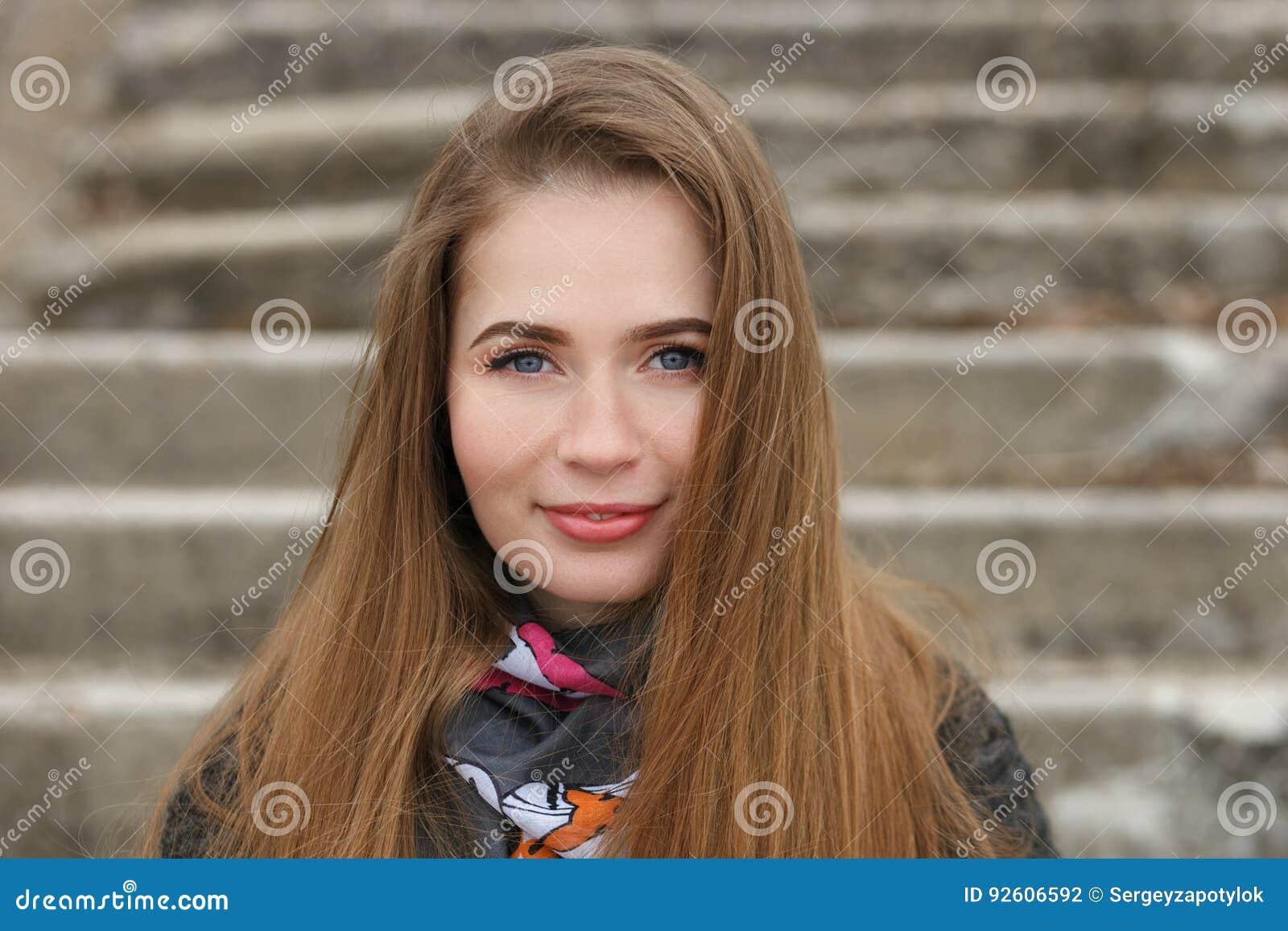Retrato do estilo de vida da mulher adulta nova e bonita de sorriso feliz com o cabelo longo lindo que levanta no parque da cidad