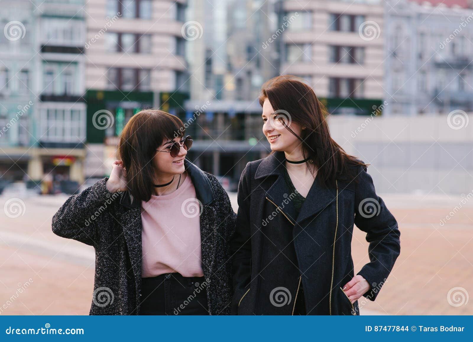 Retrato do estilo de vida da rua de dois bonitos, do sorriso e das meninas muito à moda que cidade do hulyayutpo no dia de mola