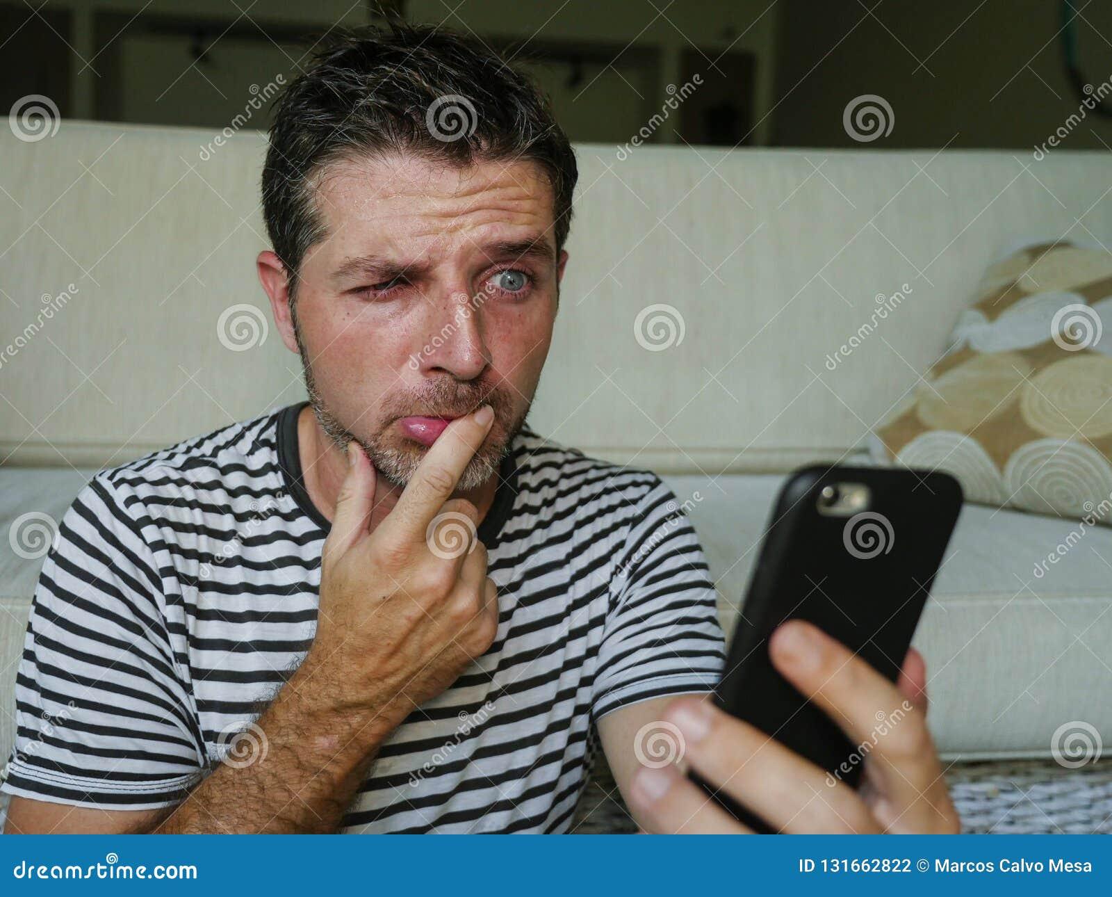 Retrato do estilo de vida do telefone celular divertido confuso e forçado novo da terra arrendada do homem que olha engraçado e p