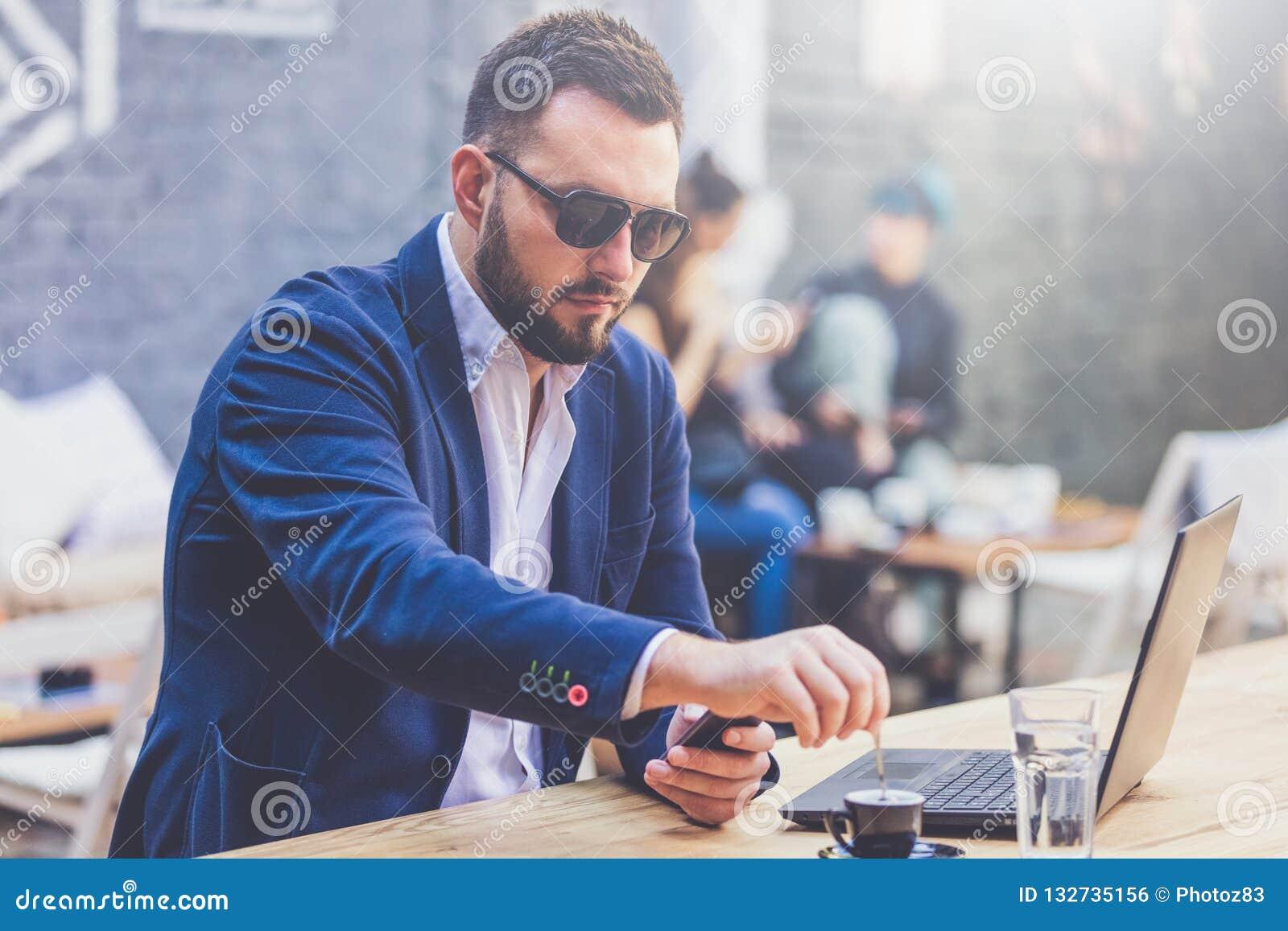 Retrato do freelancer alegre na mesa na cafetaria