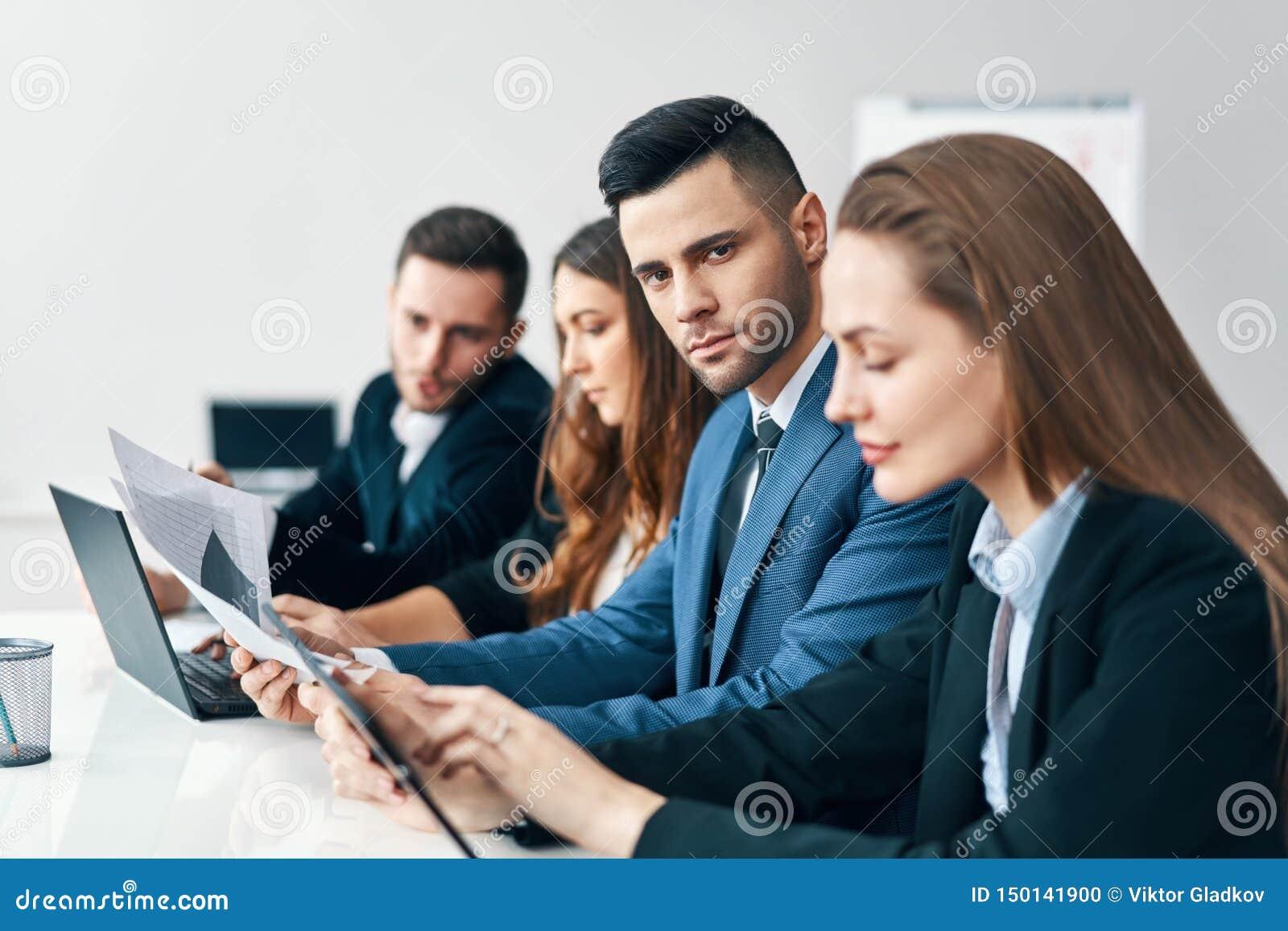 Retrato do grupo de executivos de sorriso que sentam-se em seguido junto na tabela em um escritório moderno