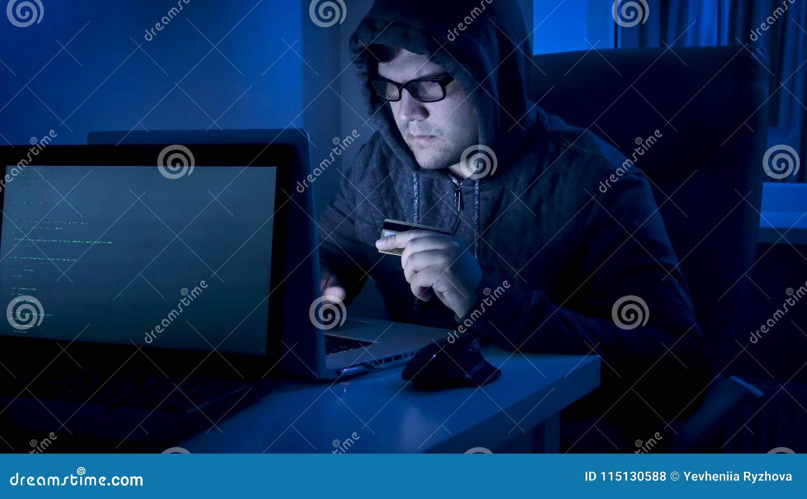 Retrato do hacker masculino que guarda o cartão de crédito e que datilografa o código do programa da fraude no portátil
