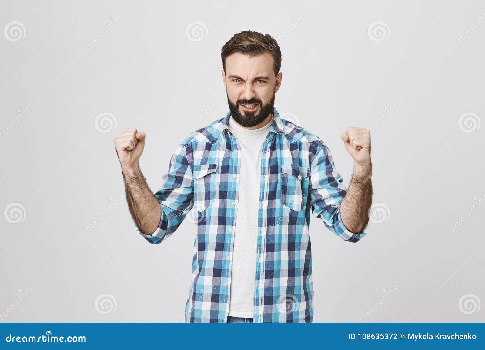 Retrato do homem adulto atlético considerável que mostra o poder e os músculos ao vestir a camisa de manta, estando sobre o cinza