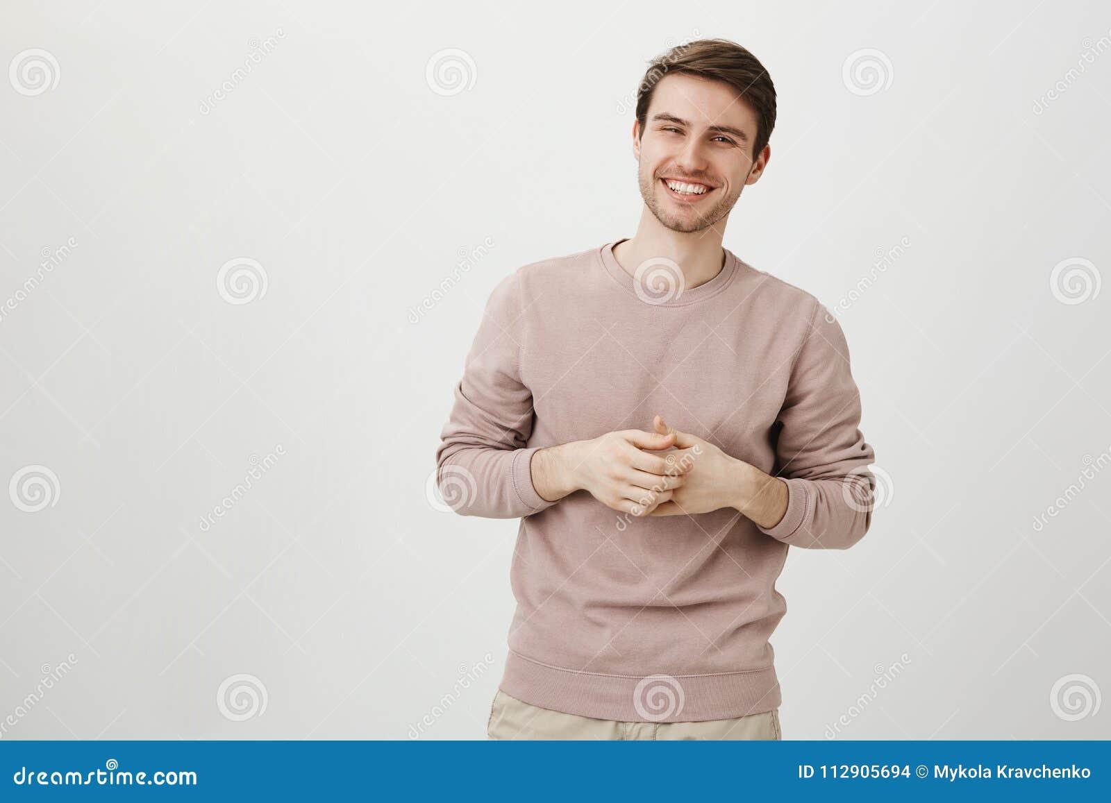 Retrato do homem atlético considerável com o sorriso encantador que guarda as mãos perto da caixa, estando no cargo ocasional com