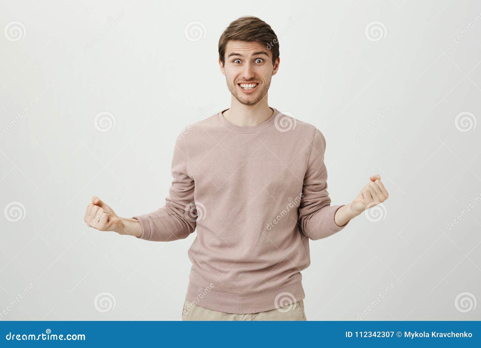 Retrato do homem bonito caucasiano positivo brincalhão com a cerda que espreme os punhos ao ser entusiasmado e ao dizer sim