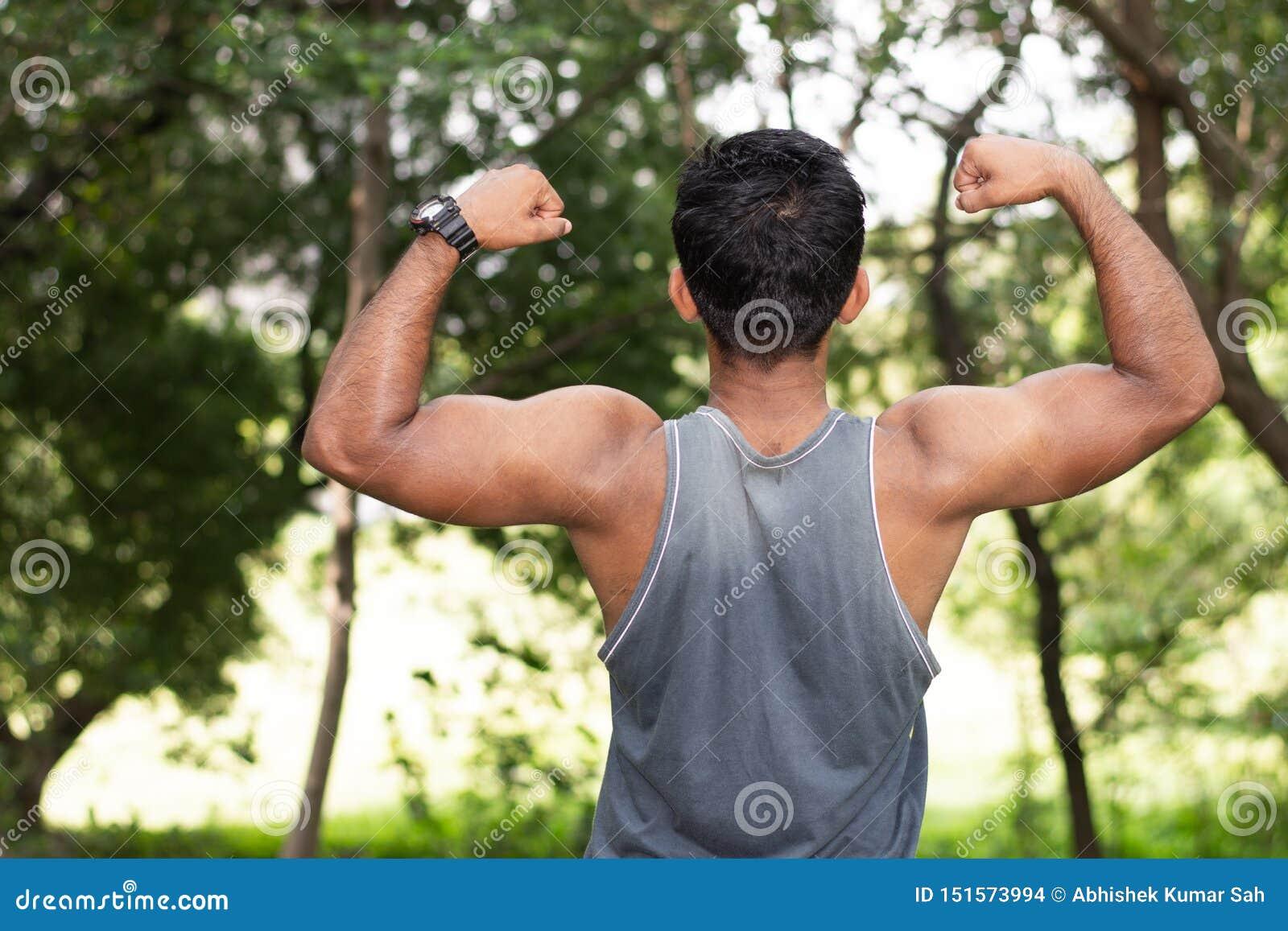 Retrato do homem caucasiano apto dos jovens com o corpo muscular que mostra o bíceps fora no dia de verão ensolarado no parque