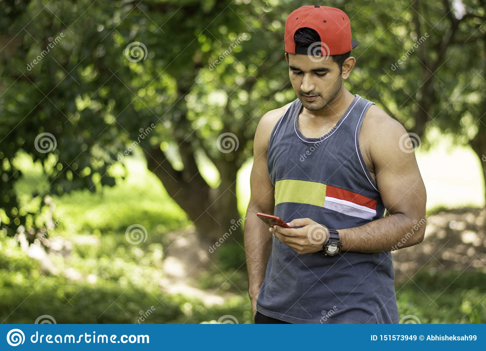 Retrato do homem caucasiano apto novo com o corpo muscular que usa o ar livre do smartphone no dia de verão ensolarado