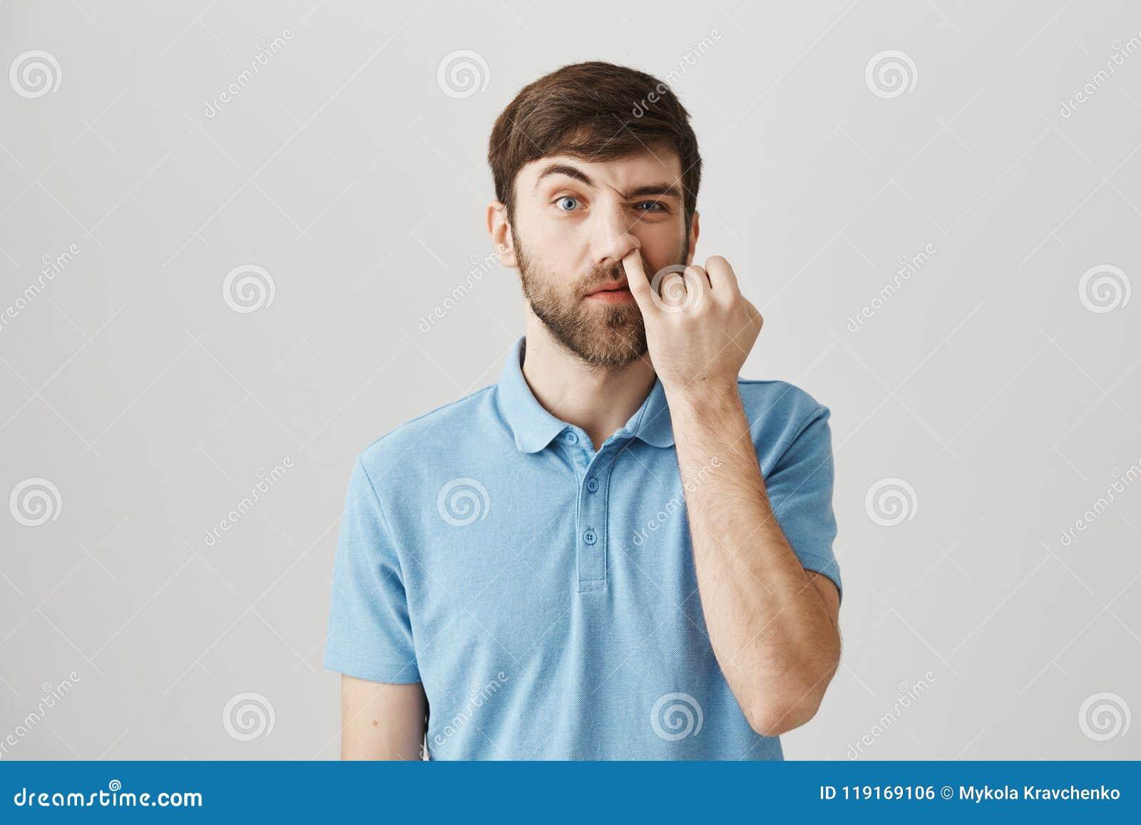 Retrato do homem caucasiano descortês engraçado com barba, escolhendo o nariz com olhar fixamente mindinho com a sobrancelha leva