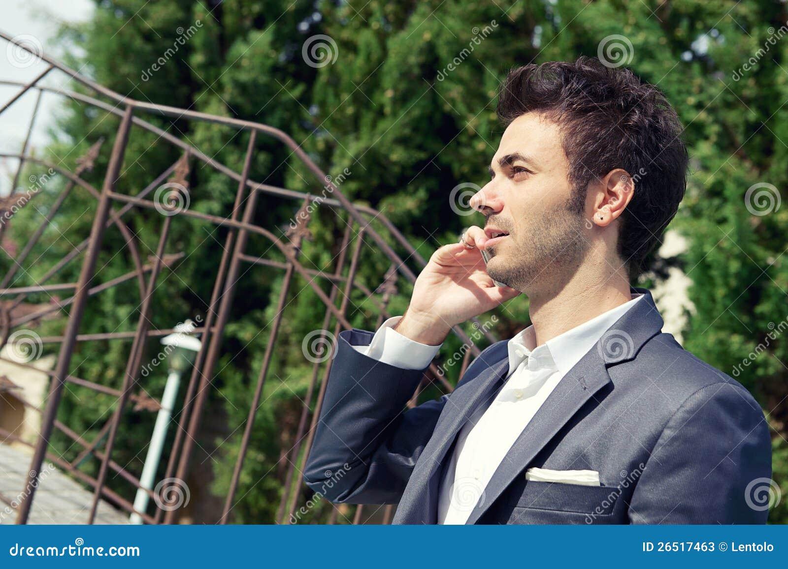 Retrato do homem de negócio novo que usa o móbil