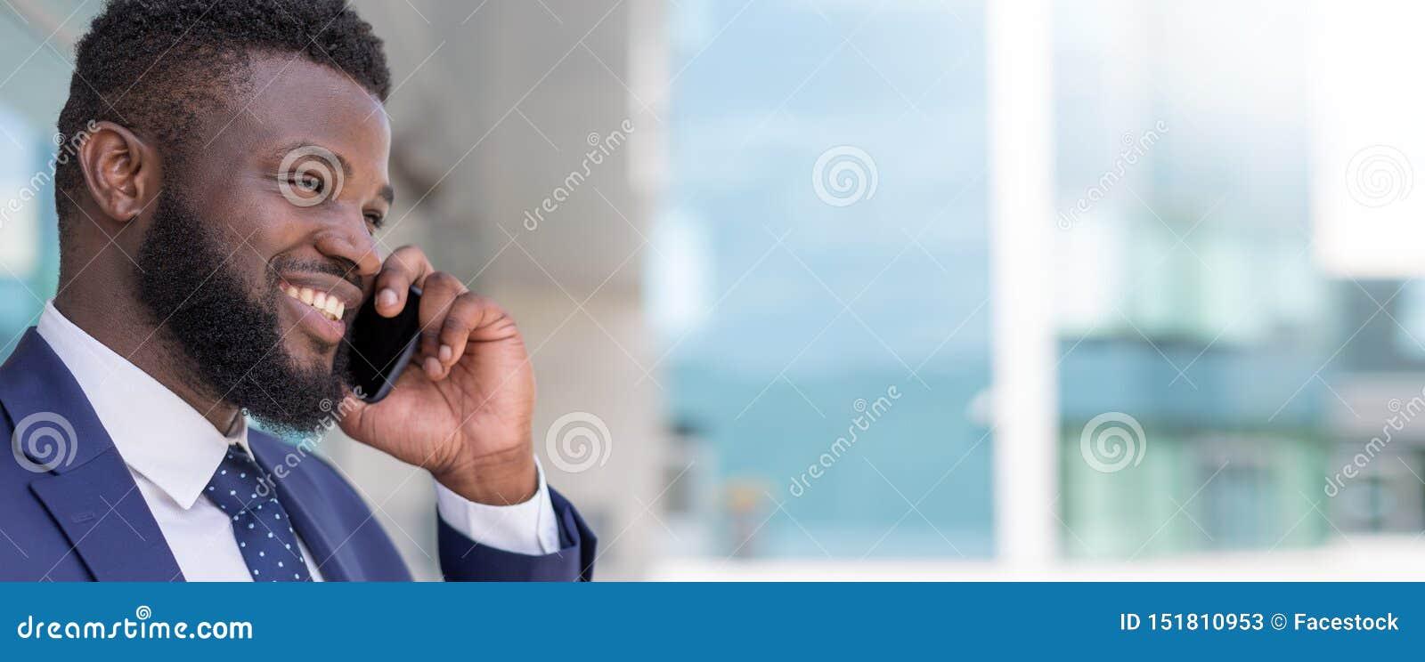 Retrato do homem de negócios africano de sorriso que fala pelo telefone fora com espaço da cópia