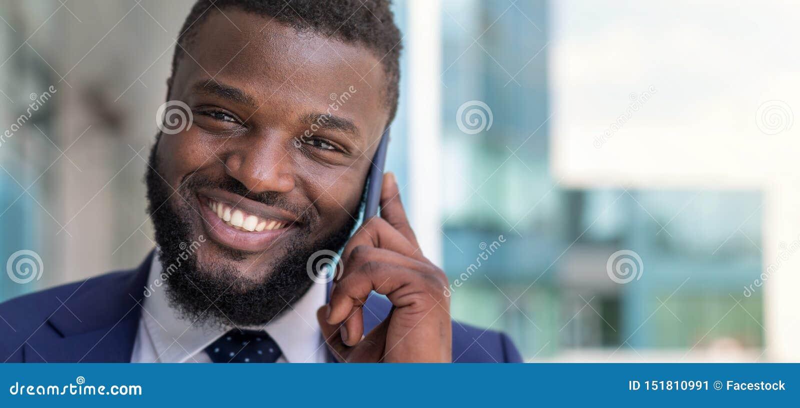 Retrato do homem de negócios afro-americano de sorriso que fala pelo telefone fora Copie o espa?o