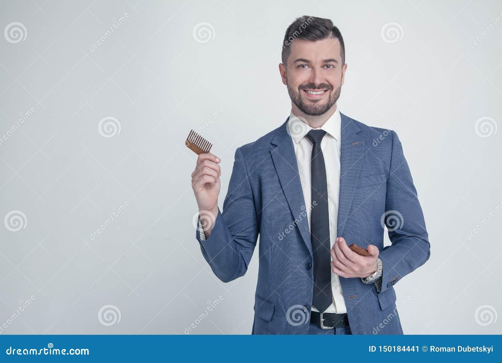 Retrato do homem de negócios atrativo novo com olhar de sorriso, guardando o pente de madeira Barbeiro farpado à moda no terno qu