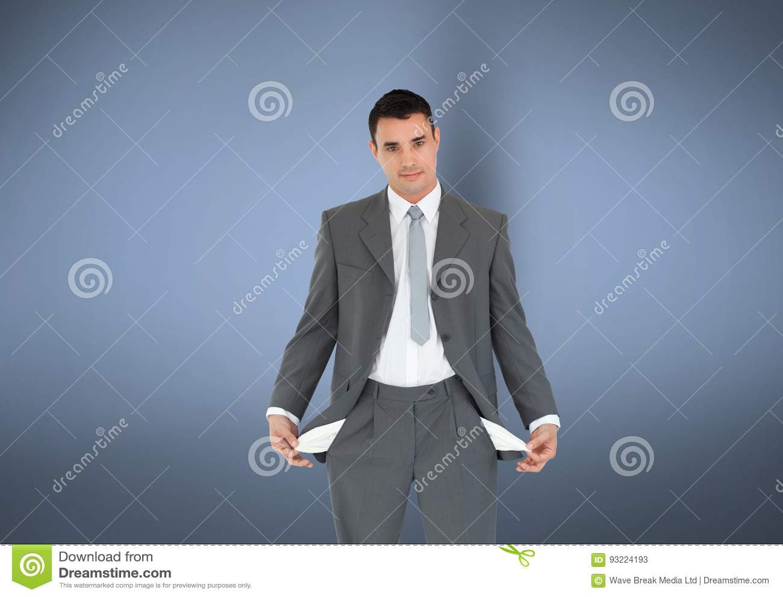 Retrato do homem de negócios com os bolsos vazios que estão contra o fundo cinzento que não representa nenhum dinheiro