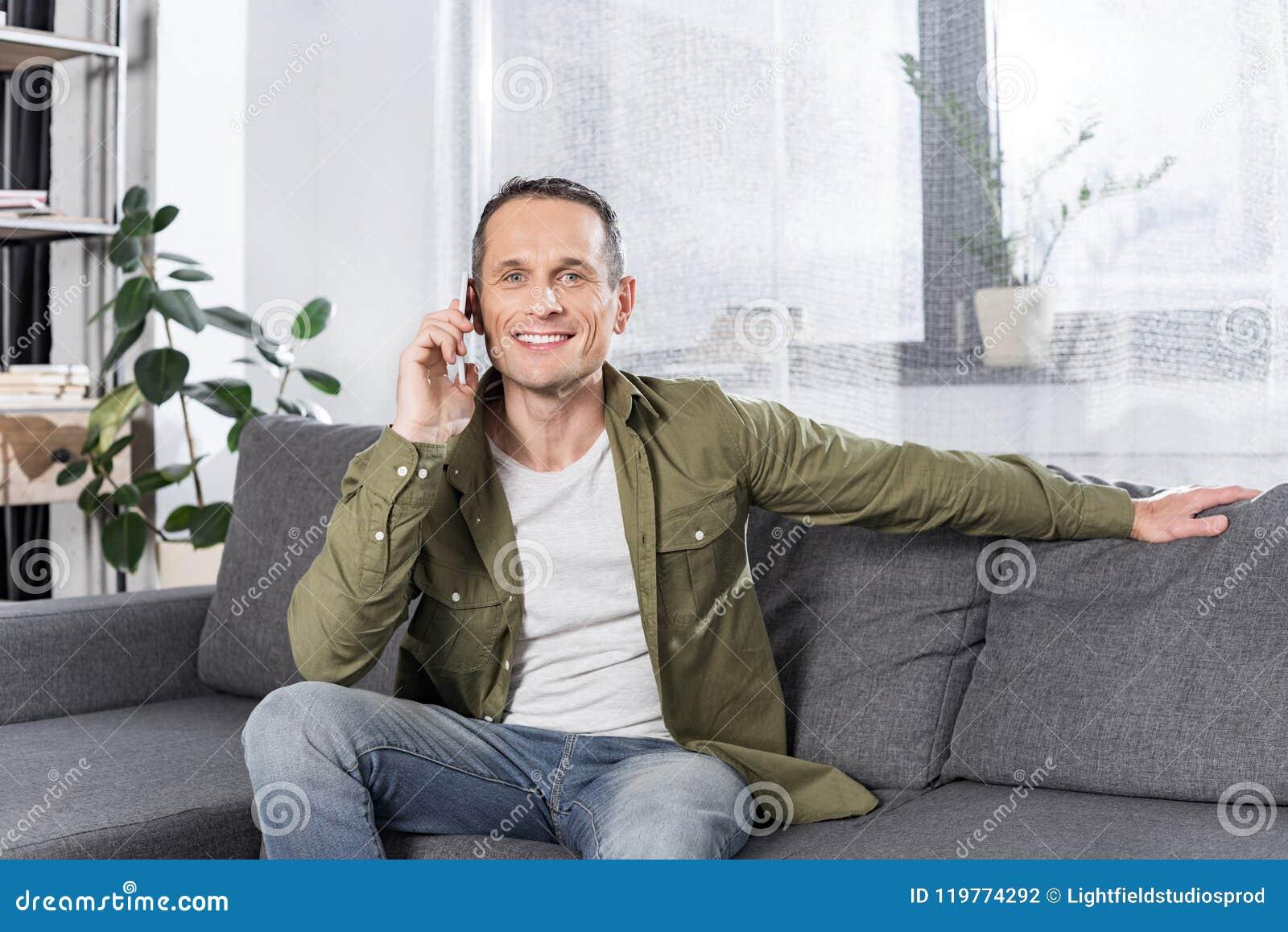 Retrato do homem de sorriso que fala no smartphone ao descansar no sofá