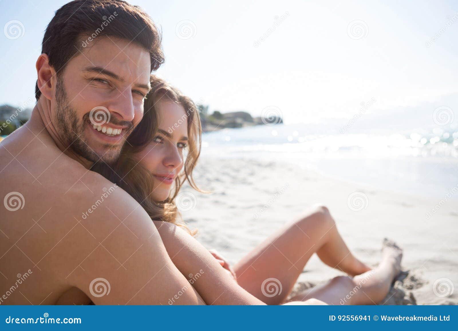 Retrato do homem descamisado novo com sua amiga que senta-se na praia