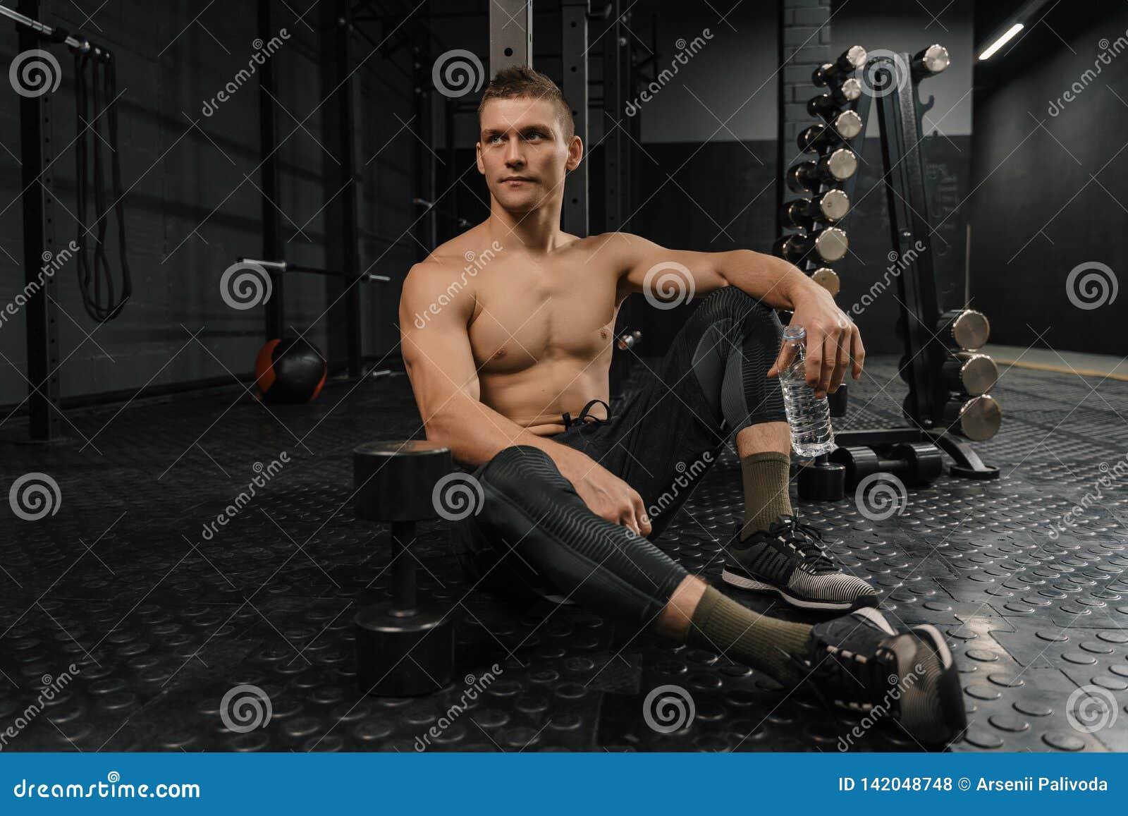 Retrato do homem desportivo novo com resto da garrafa no gym após o exercício