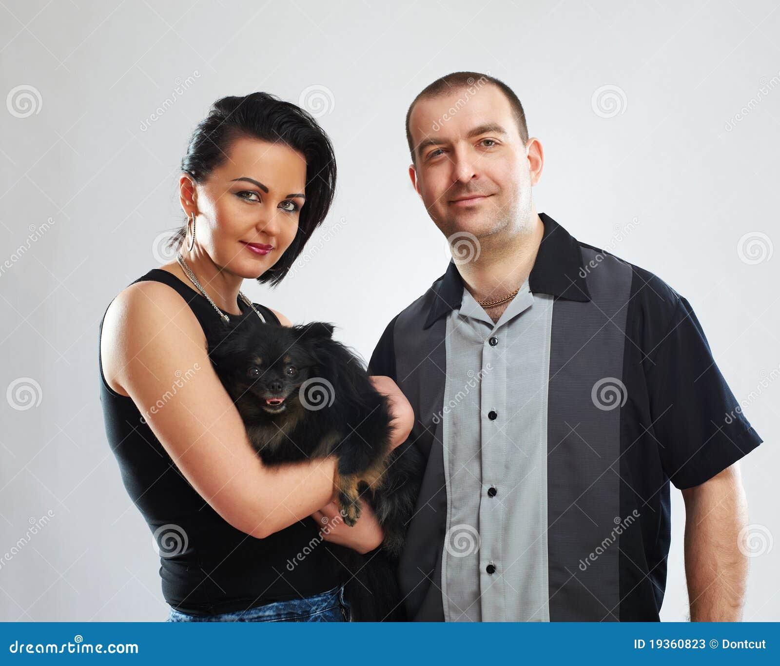 Retrato do homem e da mulher com um cão preto pequeno