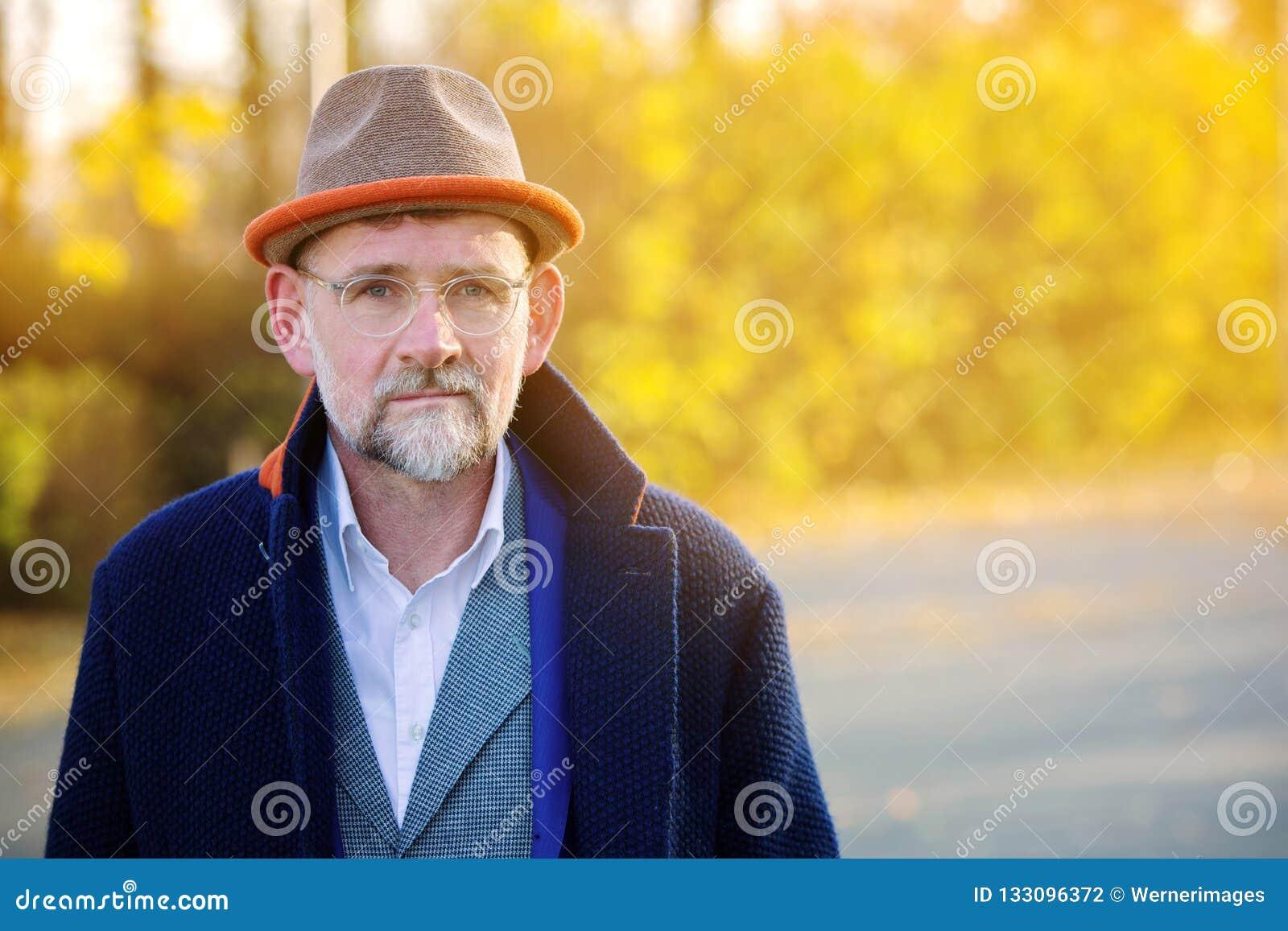 Retrato do homem em seu 50s no ar livre azul do terno e do revestimento