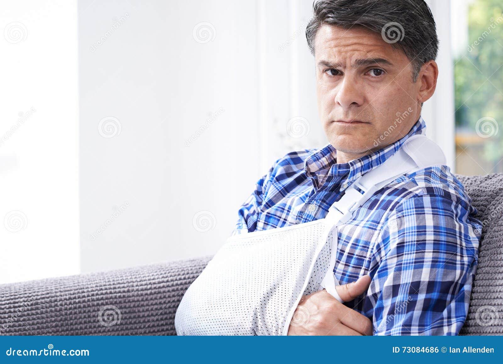 Retrato do homem maduro com o braço no estilingue em casa