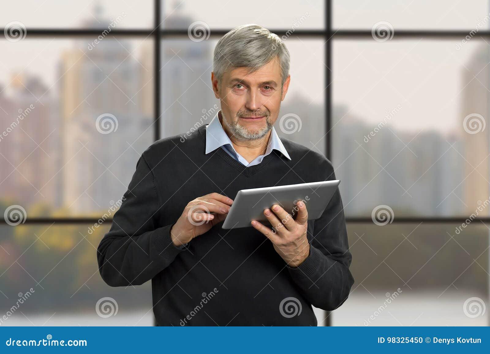 Retrato do homem maduro com tabuleta do PC