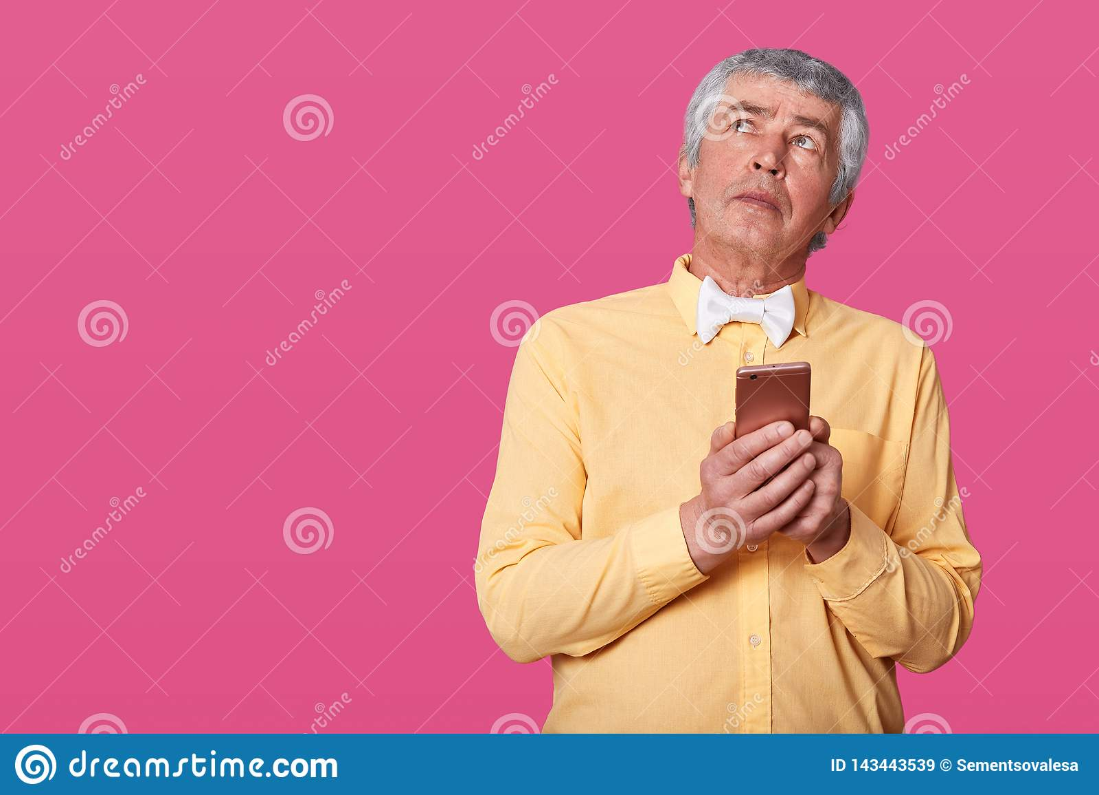 Retrato do homem maduro que tem enrugamentos e o cabelo cinzento vestidos na camisa amarela e no laço branco, guardando o smartph