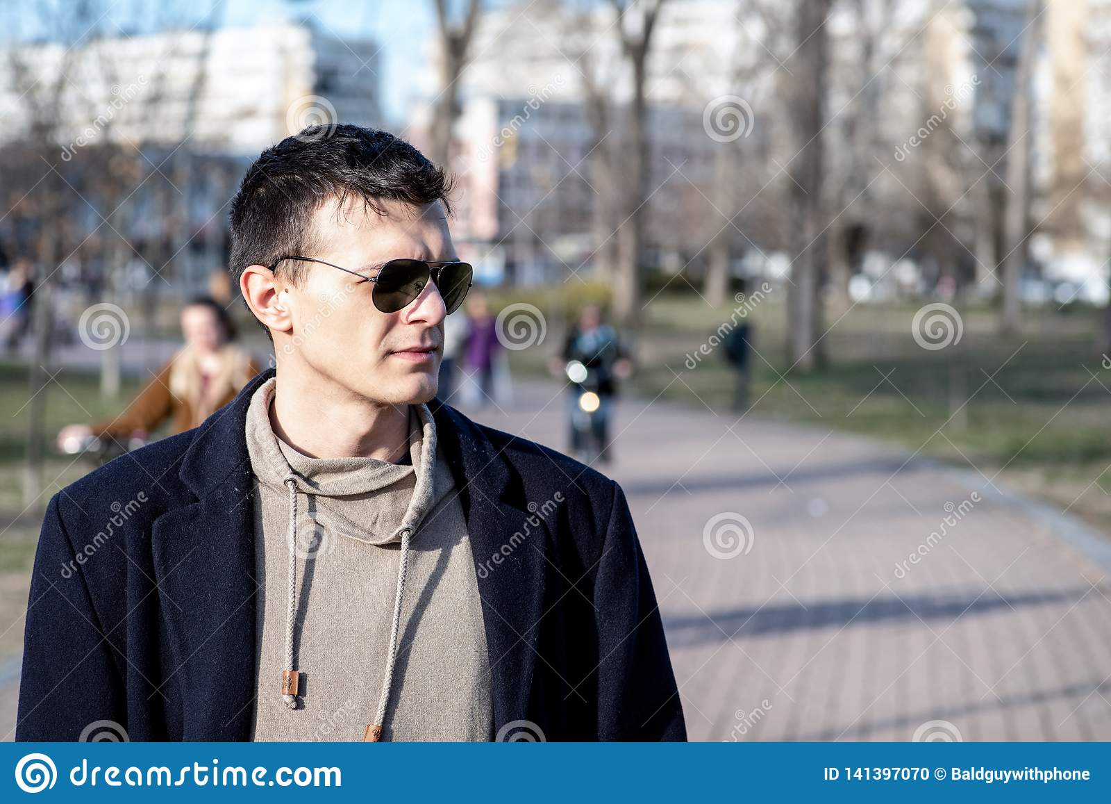 Retrato do homem novo com os óculos de sol e o revestimento preto exteriores no parque