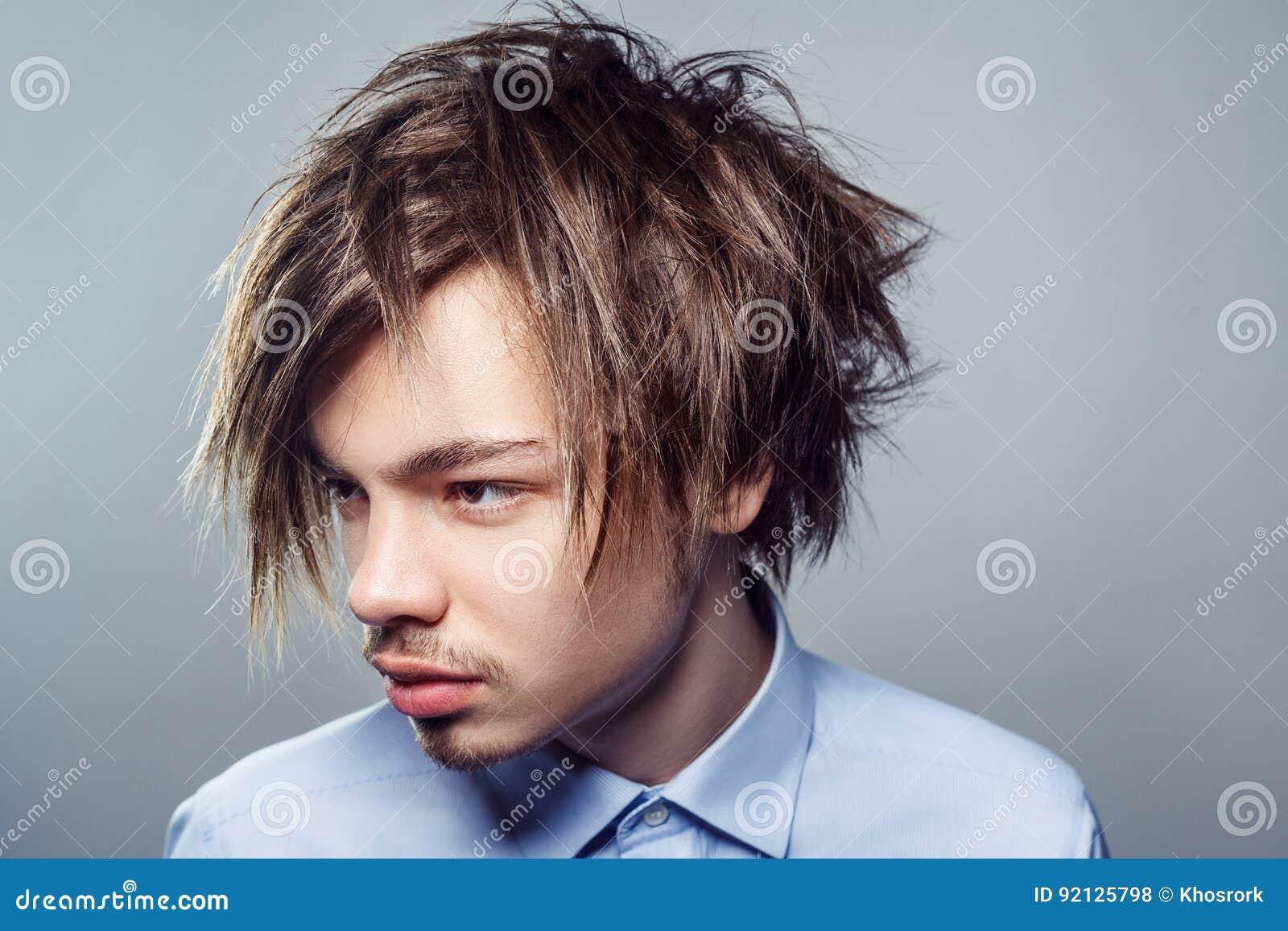 Retrato do homem novo com penteado desarrumado da franja Tiro do estúdio