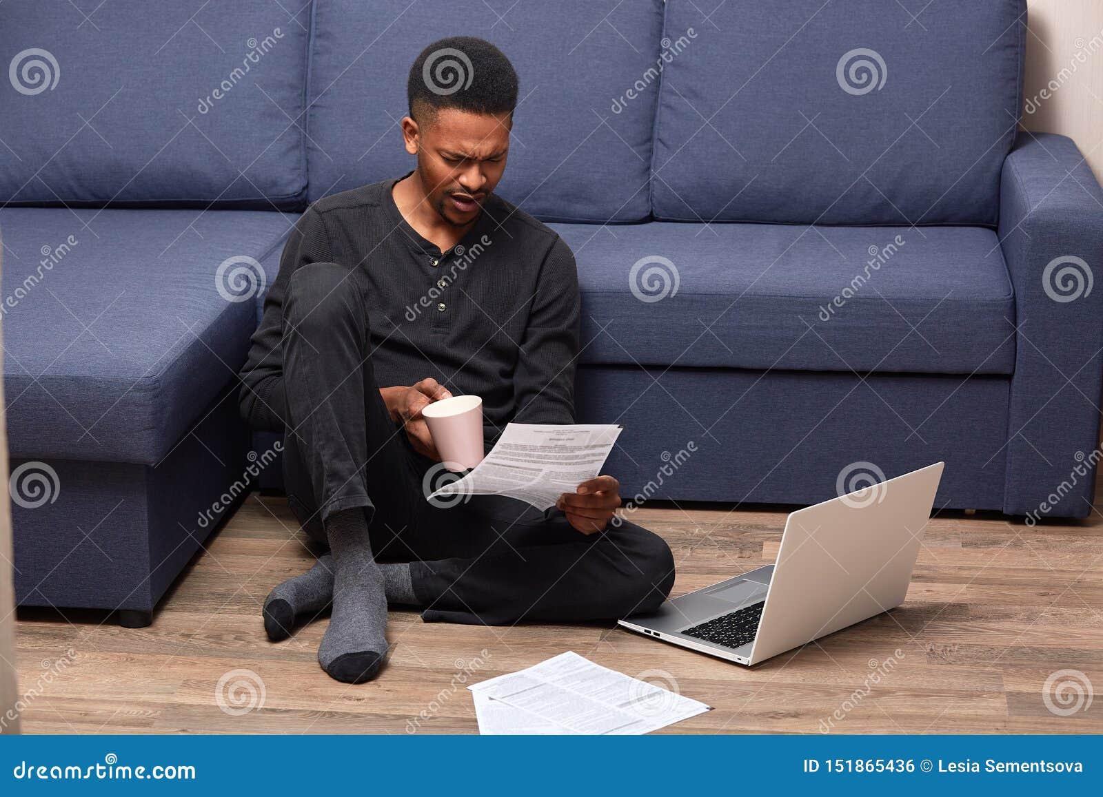 Retrato do homem novo considerável no equipamento ocasional preto, sentando-se no assoalho com laptop, trabalhando com papéis e b