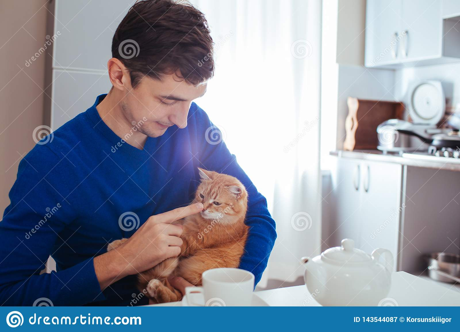 Retrato do homem novo considerável que joga com o gato na cozinha