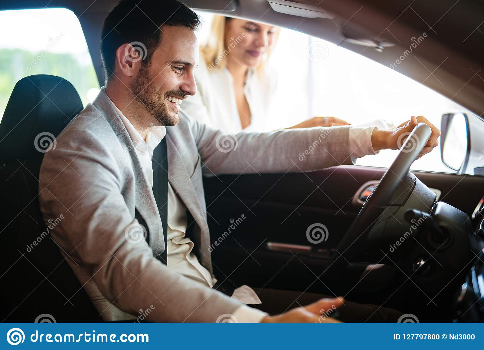 Retrato do homem novo considerável que toma o carro luxuoso para a movimentação, o assento interno e o sorriso do teste