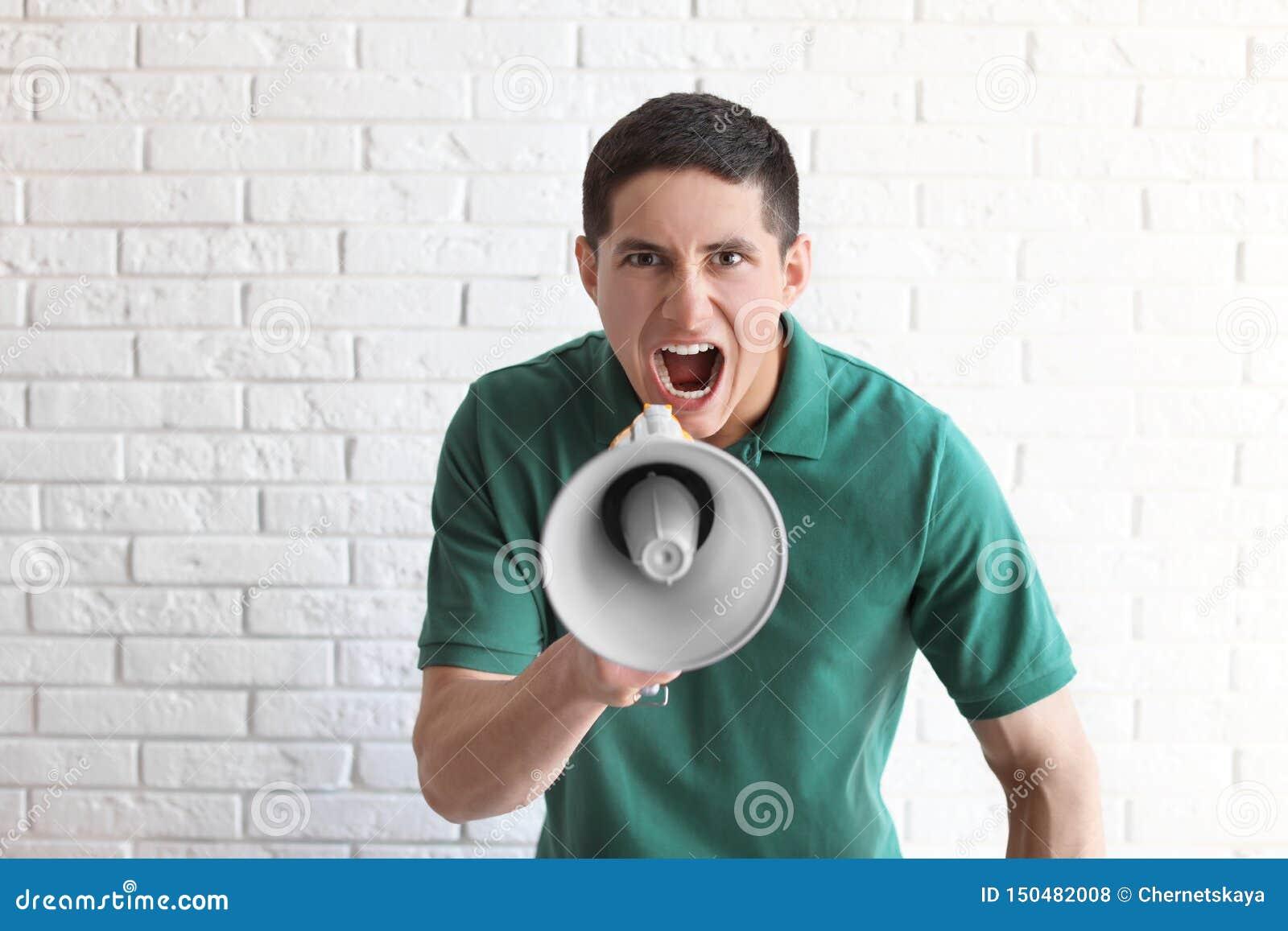 Retrato do homem novo que usa o megafone