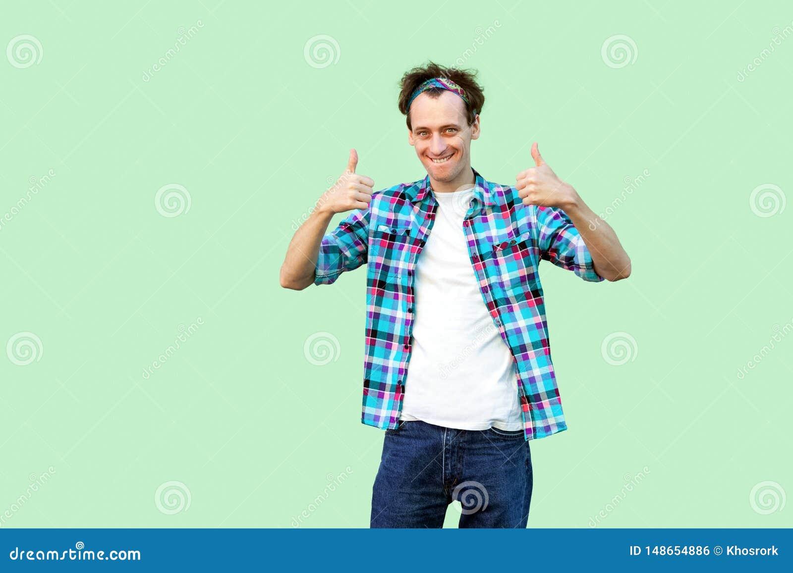 Retrato do homem novo satisfeito na posi??o quadriculado azul ocasional da camisa e da faixa, polegares acima e olhando a c?mera