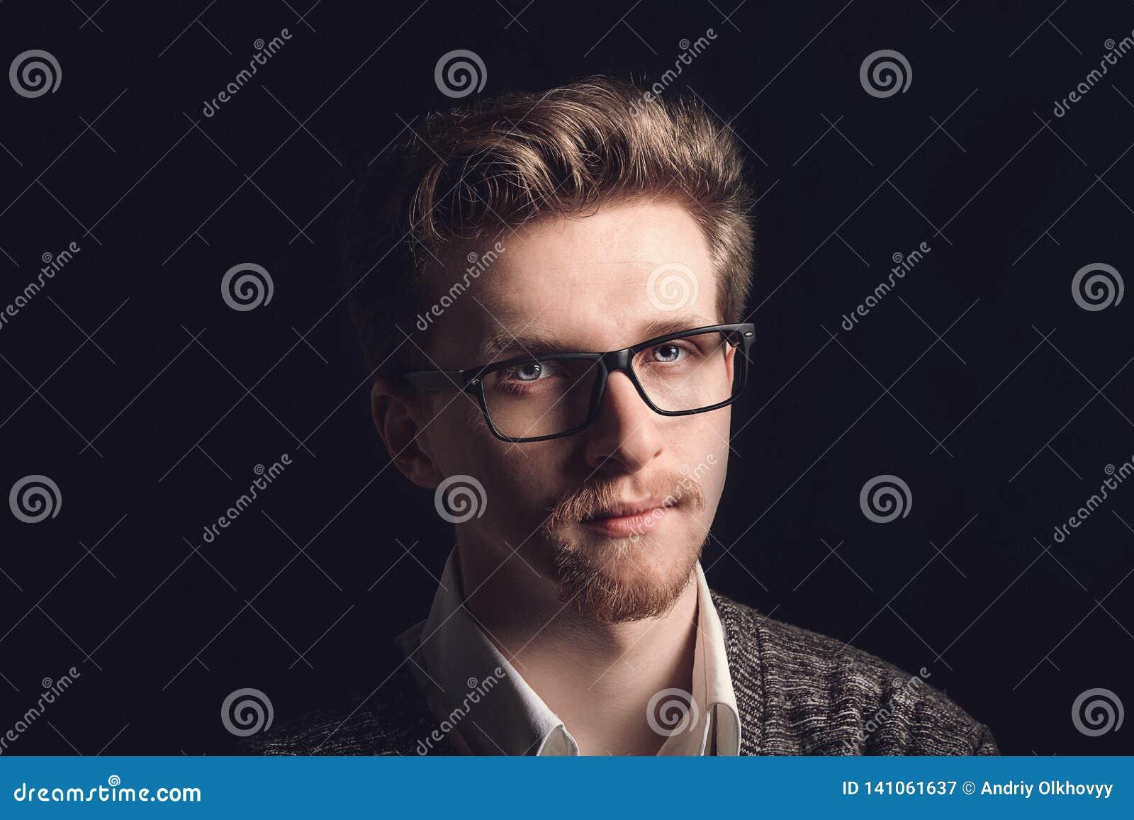 Retrato do homem ocasional novo com vidros que sorri na frente da câmera Homem considerável novo na camisa e nos vidros da marinh