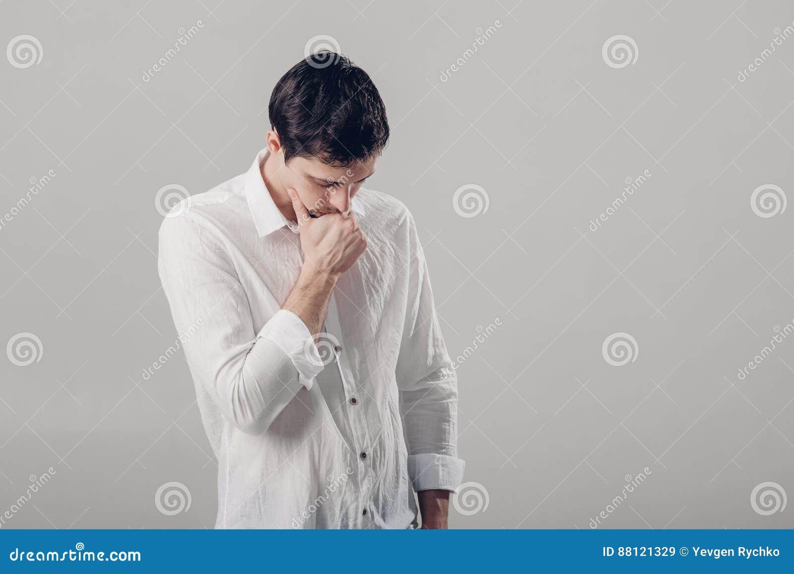 Retrato do homem pensativo novo considerável na camisa branca em vagabundos cinzentos