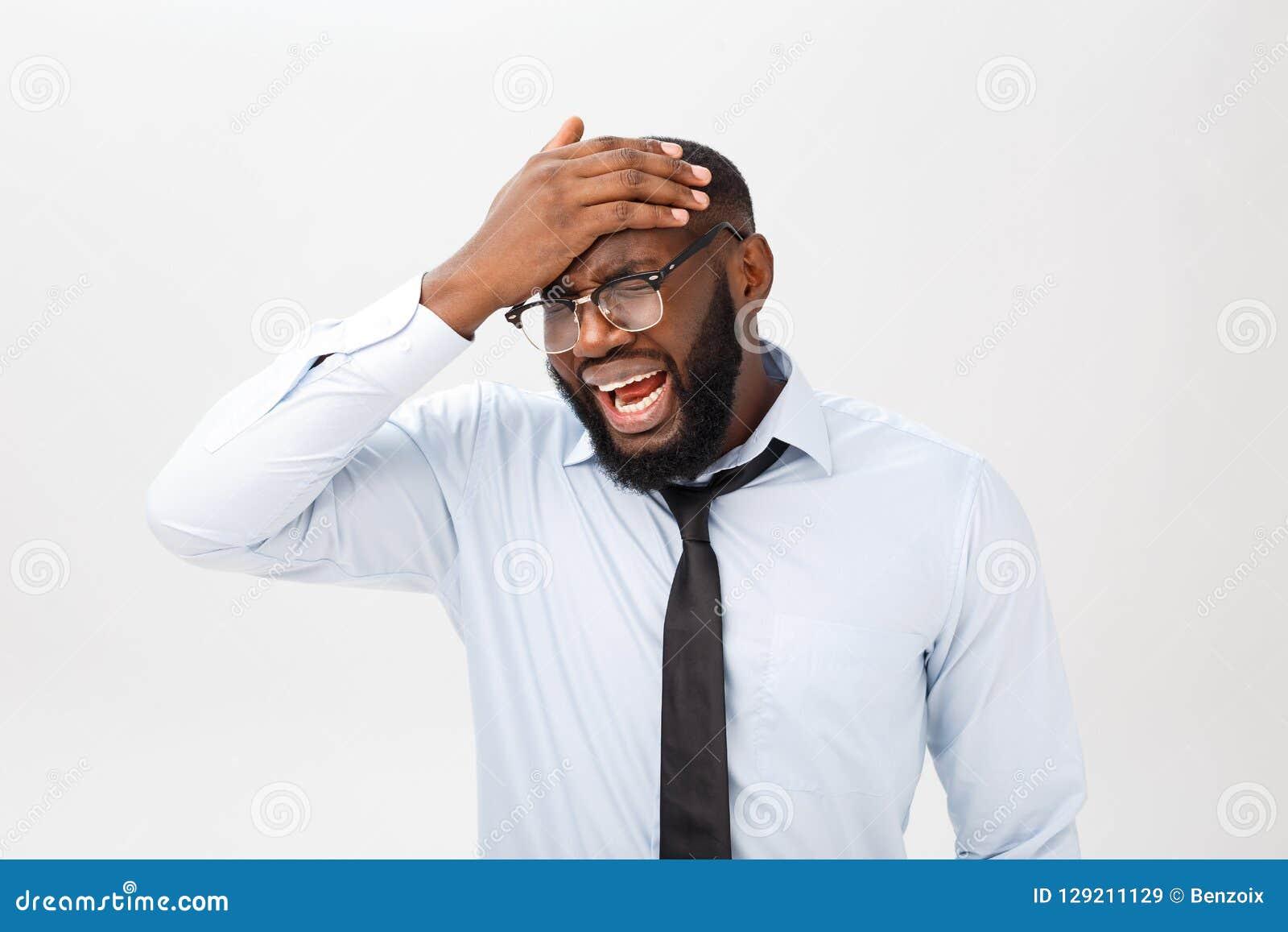 Retrato do homem preto irritado desesperado que grita na raiva e na raiva que rasgam seu cabelo para fora ao sentir furioso e lou