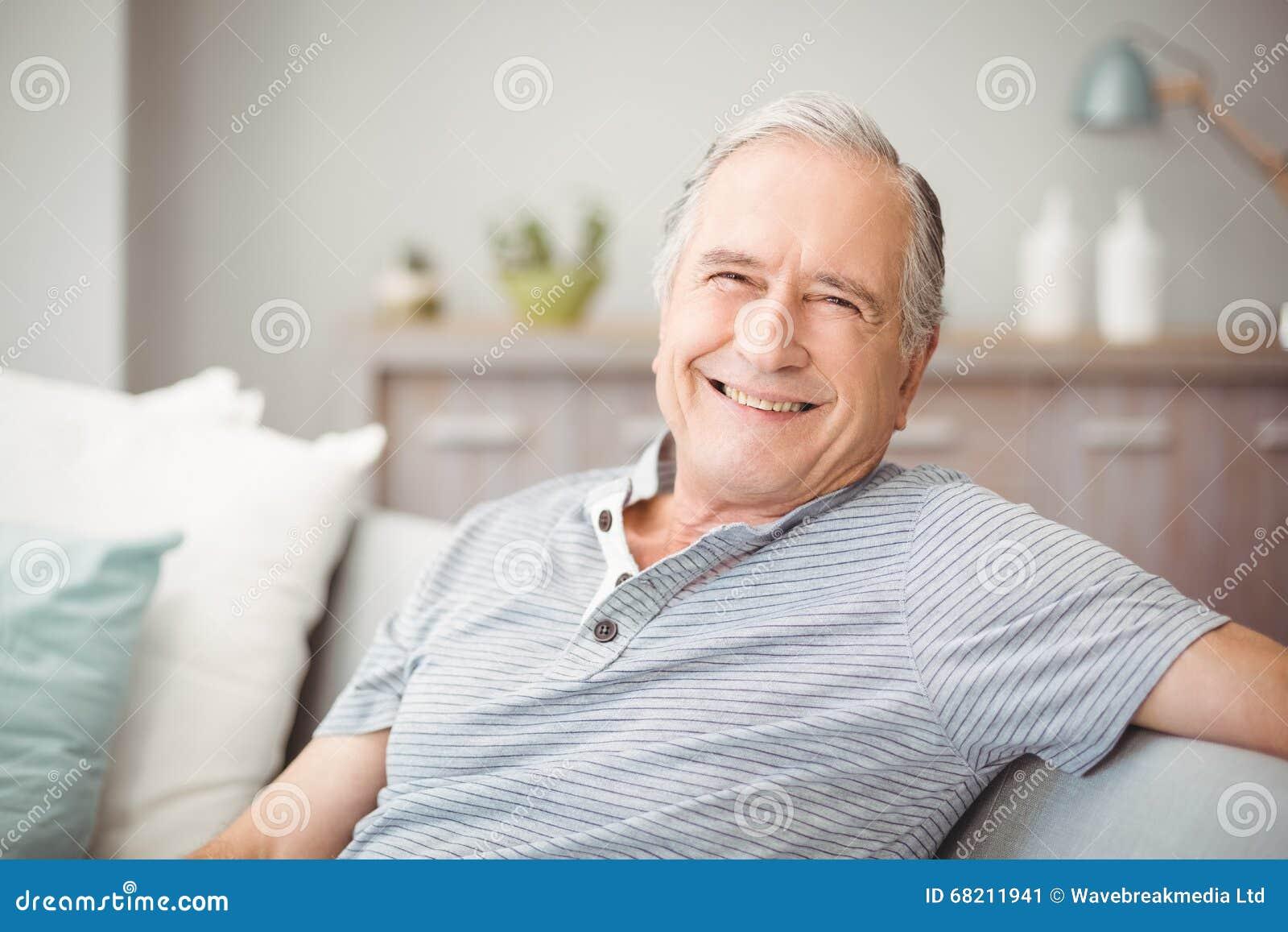 Retrato do homem superior que sorri em casa
