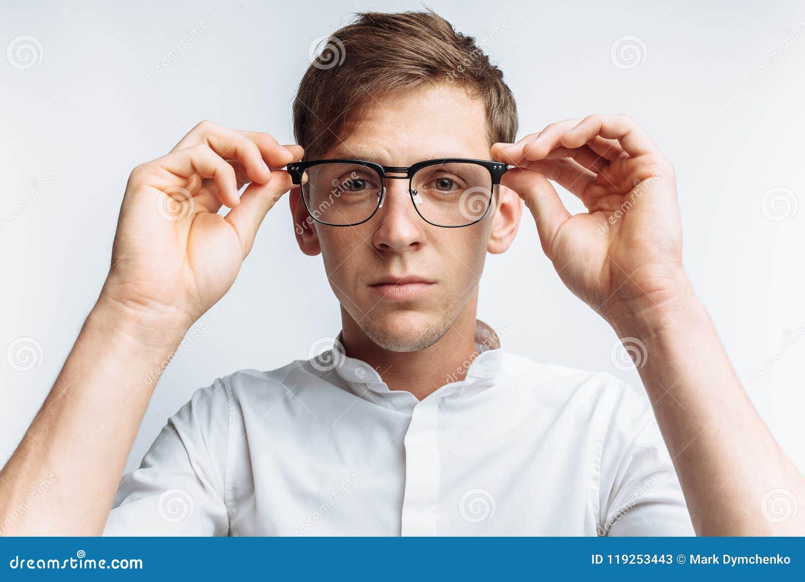 Retrato do indivíduo atrativo novo nos vidros, na camisa branca, isolada no fundo branco, para anunciar, inserção do texto