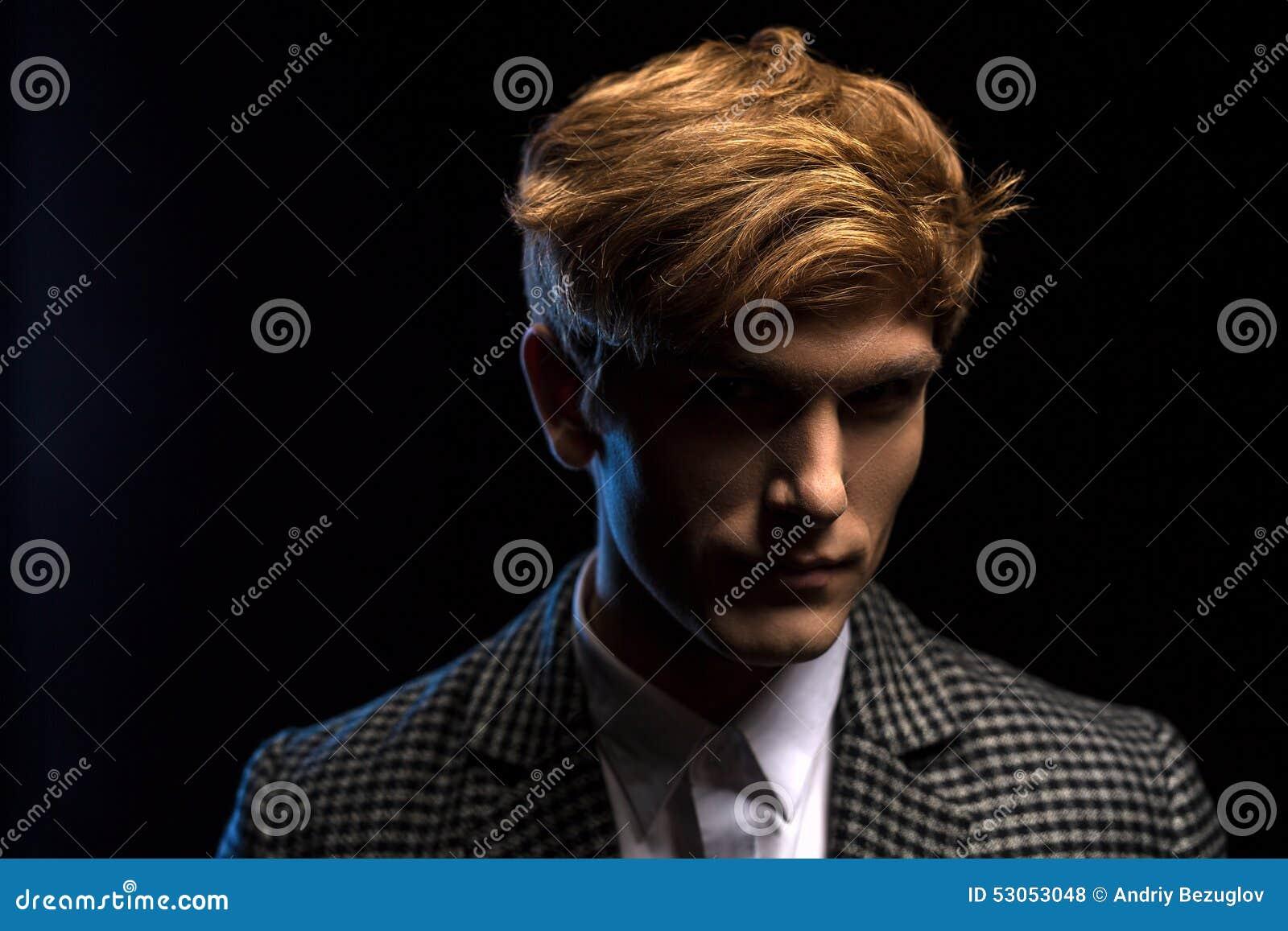 Retrato do indivíduo considerável ruivo em um preto