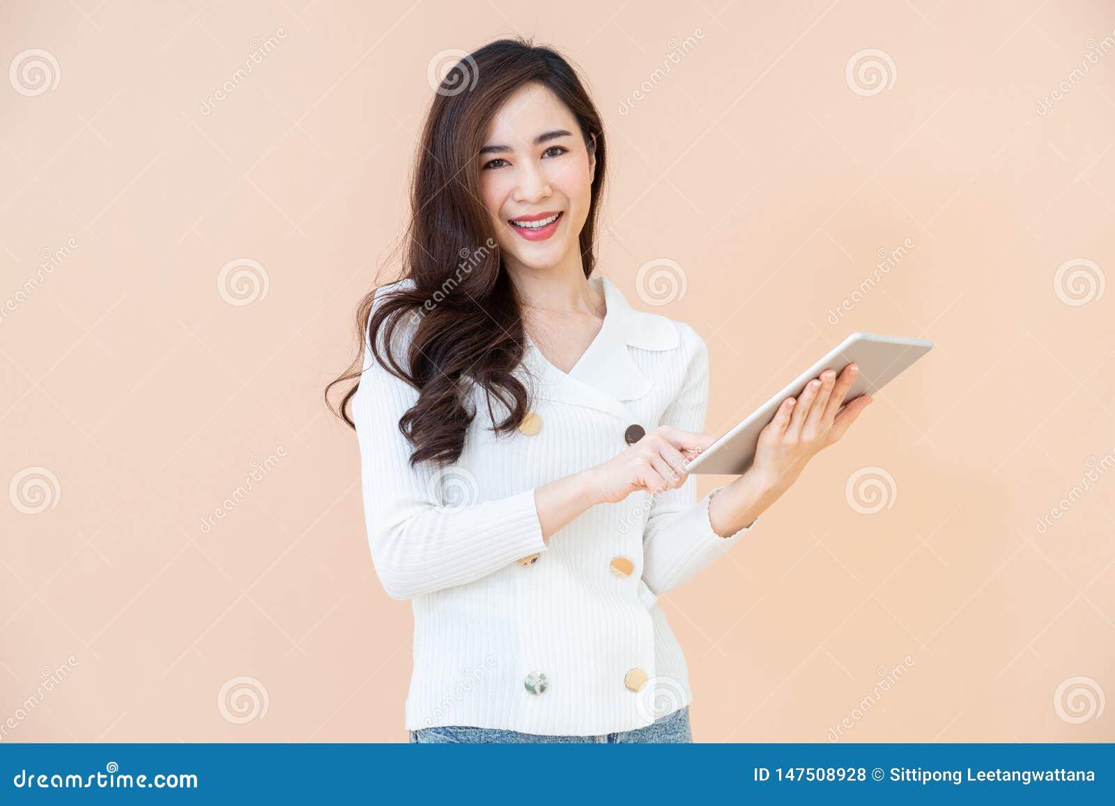 Retrato do Internet feliz de sorriso novo bonito da consultação da mulher no tablet pc digital isolado no fundo alaranjado