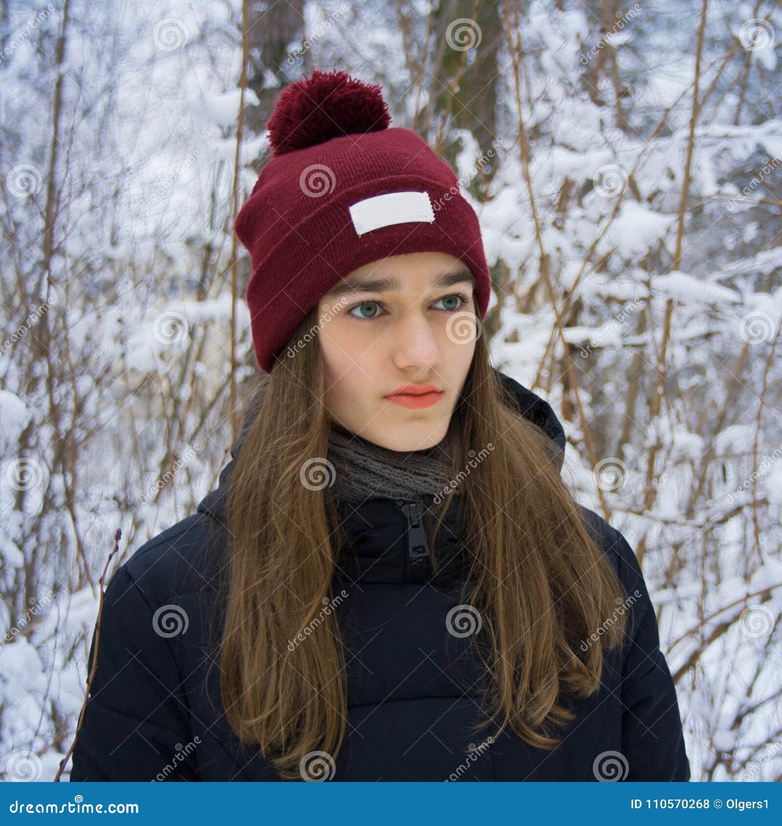 Retrato do inverno da menina adolescente na floresta nevado do inverno