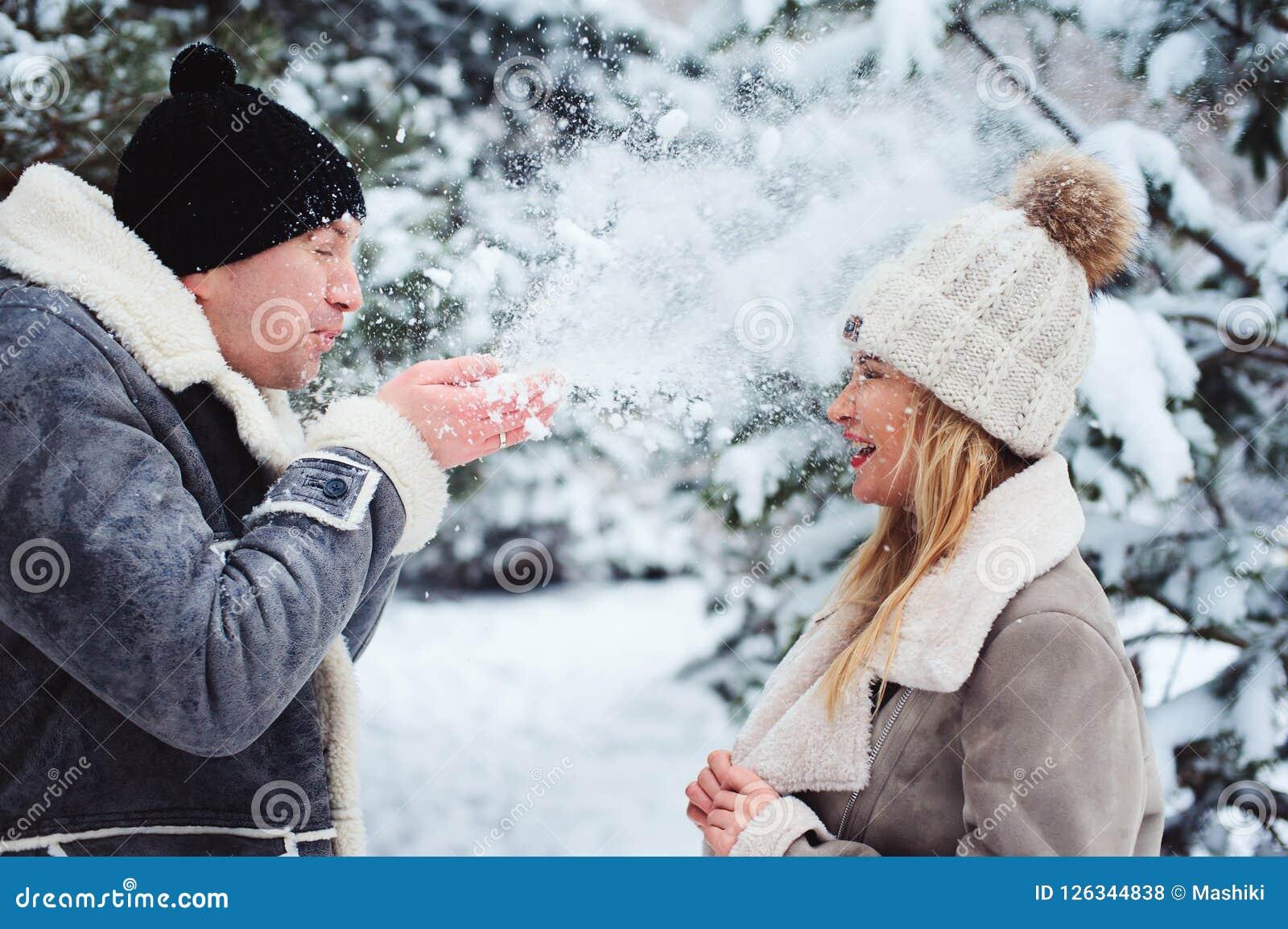 Retrato do inverno dos pares felizes neve que jogam, do sopro e passando o bom dia exterior na floresta nevado