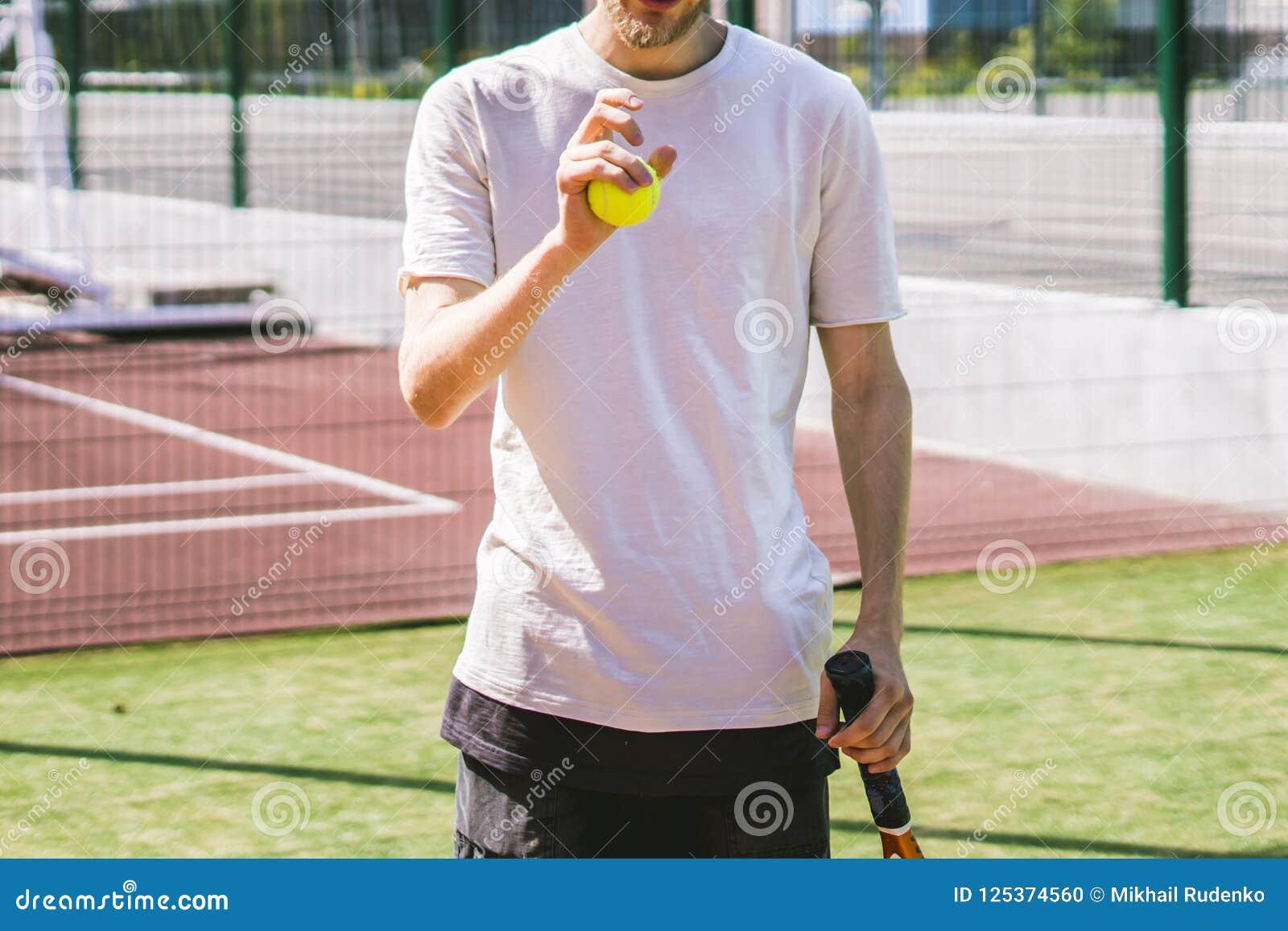 Retrato do jogador de tênis masculino novo na corte em um dia ensolarado